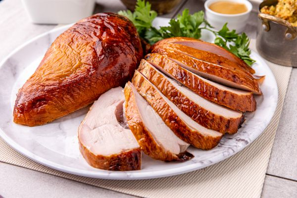 Apple and sage-brined smoked turkey breast sliced on a platter.