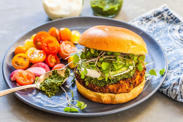 The best lentil burger is served on a plate with halved grape tomatoes and a spoon of green chutney is resting on the plate next to the burger. A patterned napkin is to the right of the plate and small glass containers of yogurt and chutney are visible above.