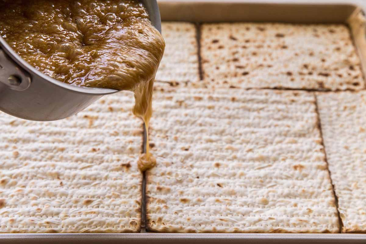 How to Make Matzo Toffee - hot toffee being poured over matzo crackers