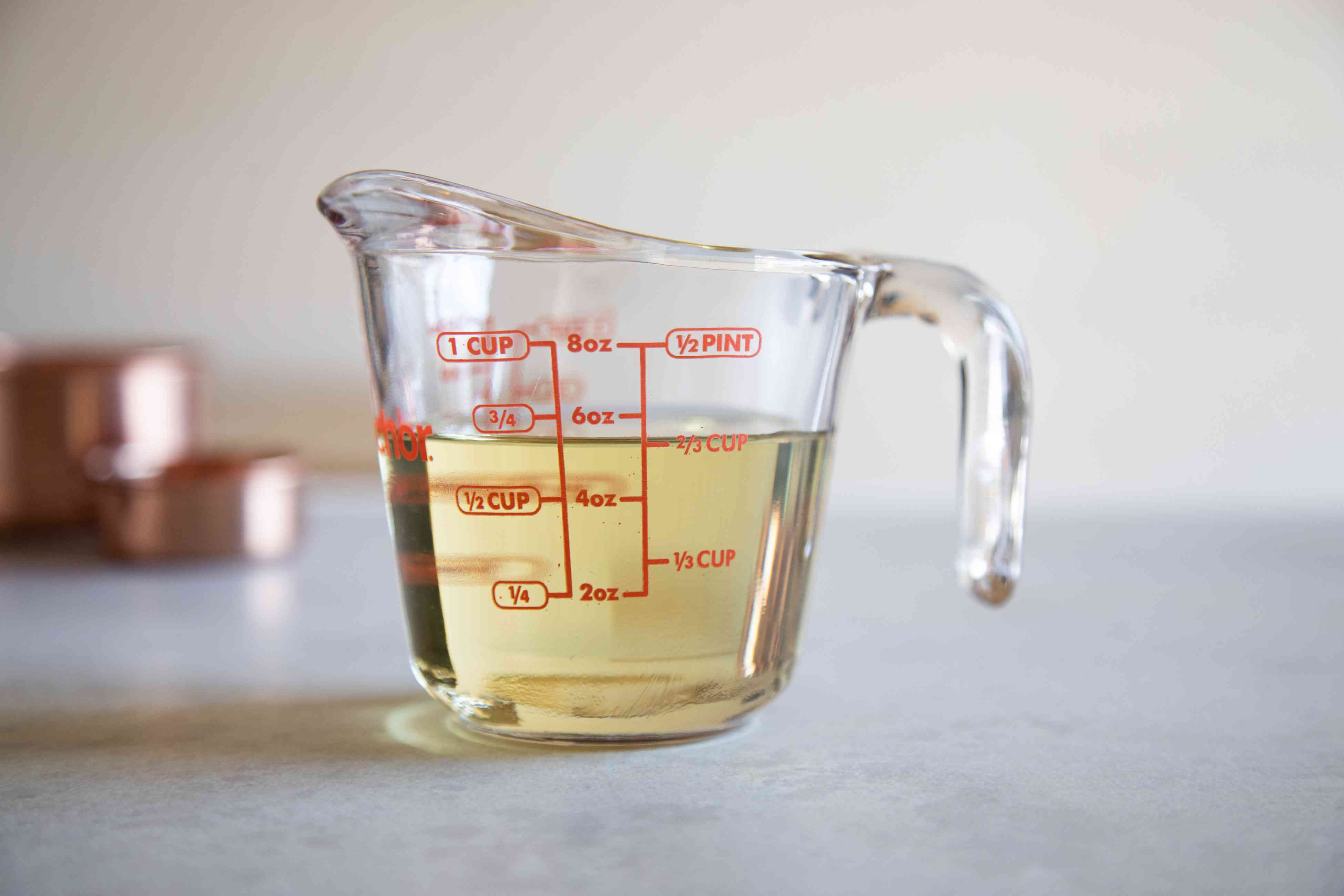 A glass measuring cup with liquid inside to show how to measure by weight and volume.
