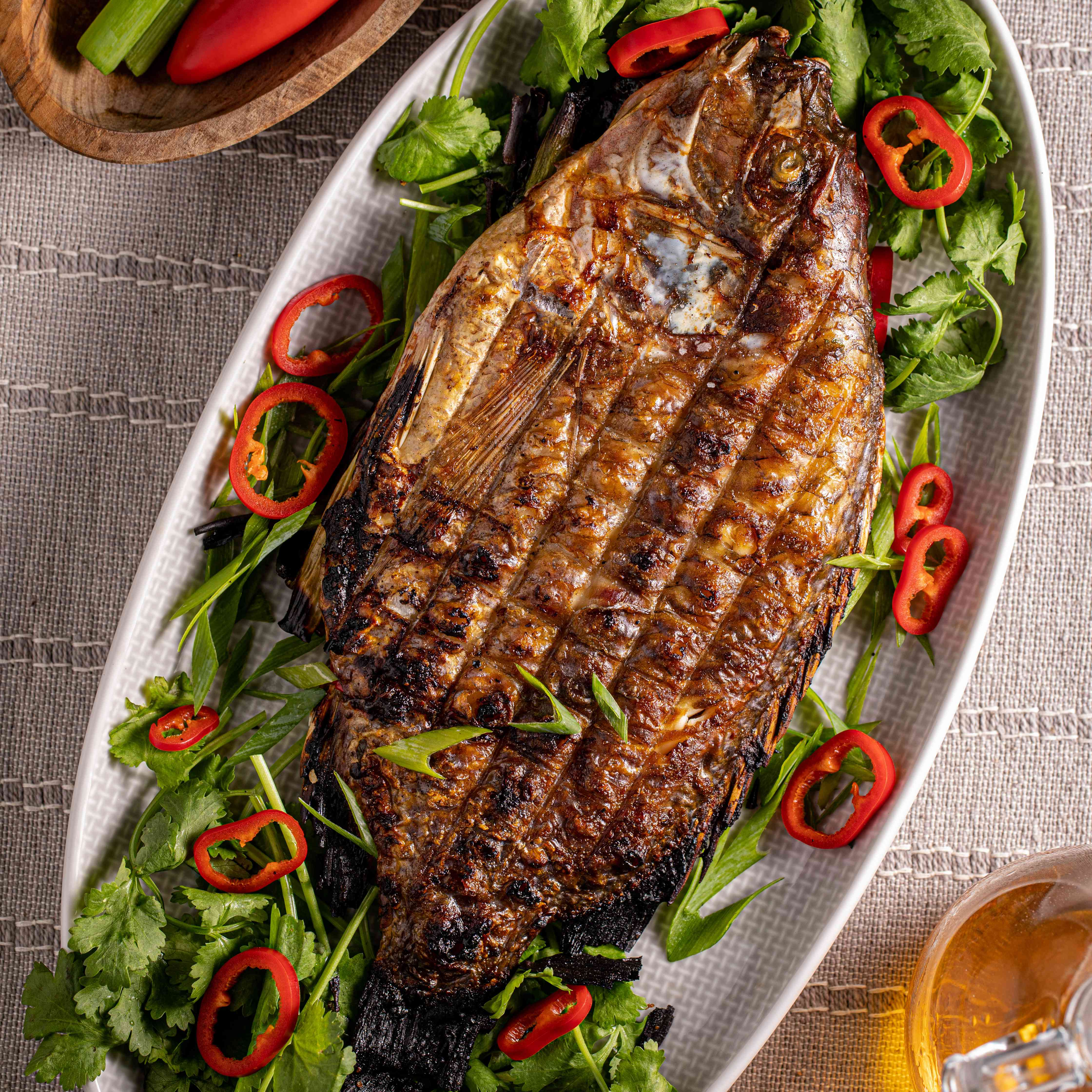 Overhead view of grilled fish stuffed with cilantro and fresno chilies on a platter.