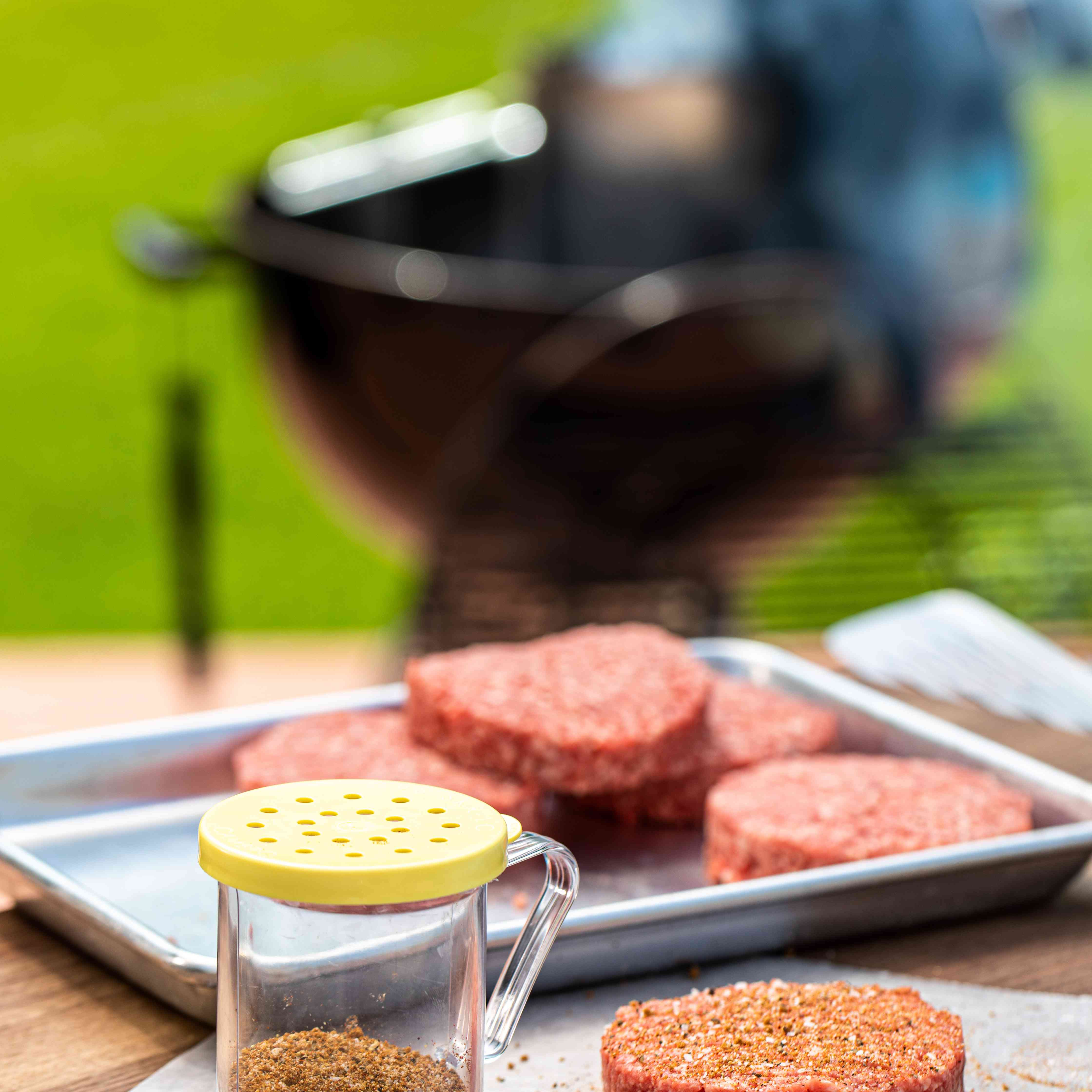 Hamburger patties set next to a jar of the best hamburger seasoning and a grill in the background.