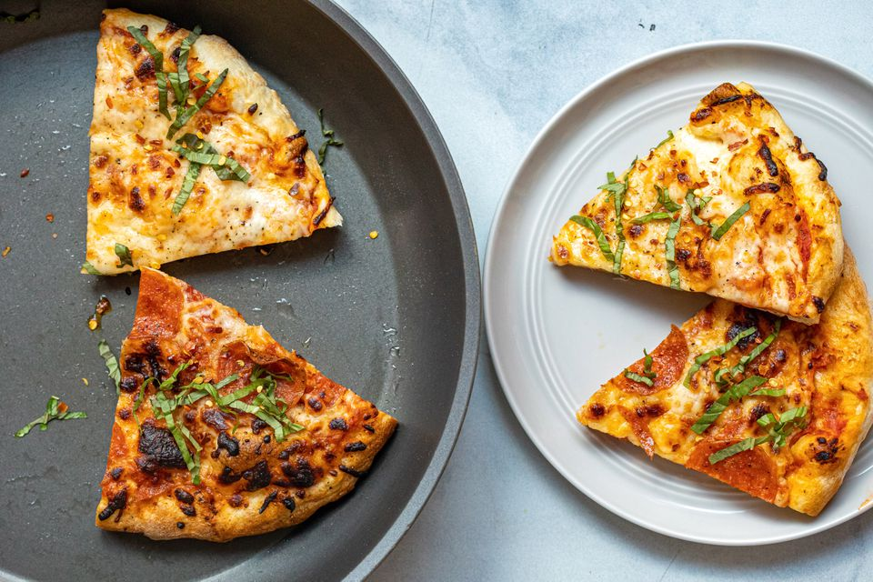 Pizza in a skillet and pizza on a white plate