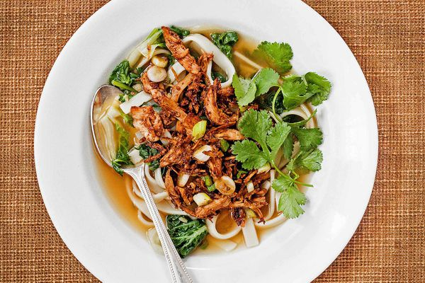 Spicy Gochujang Chicken and Udon Noodle Soup in a white bowl with a spoon and fresh herbs.