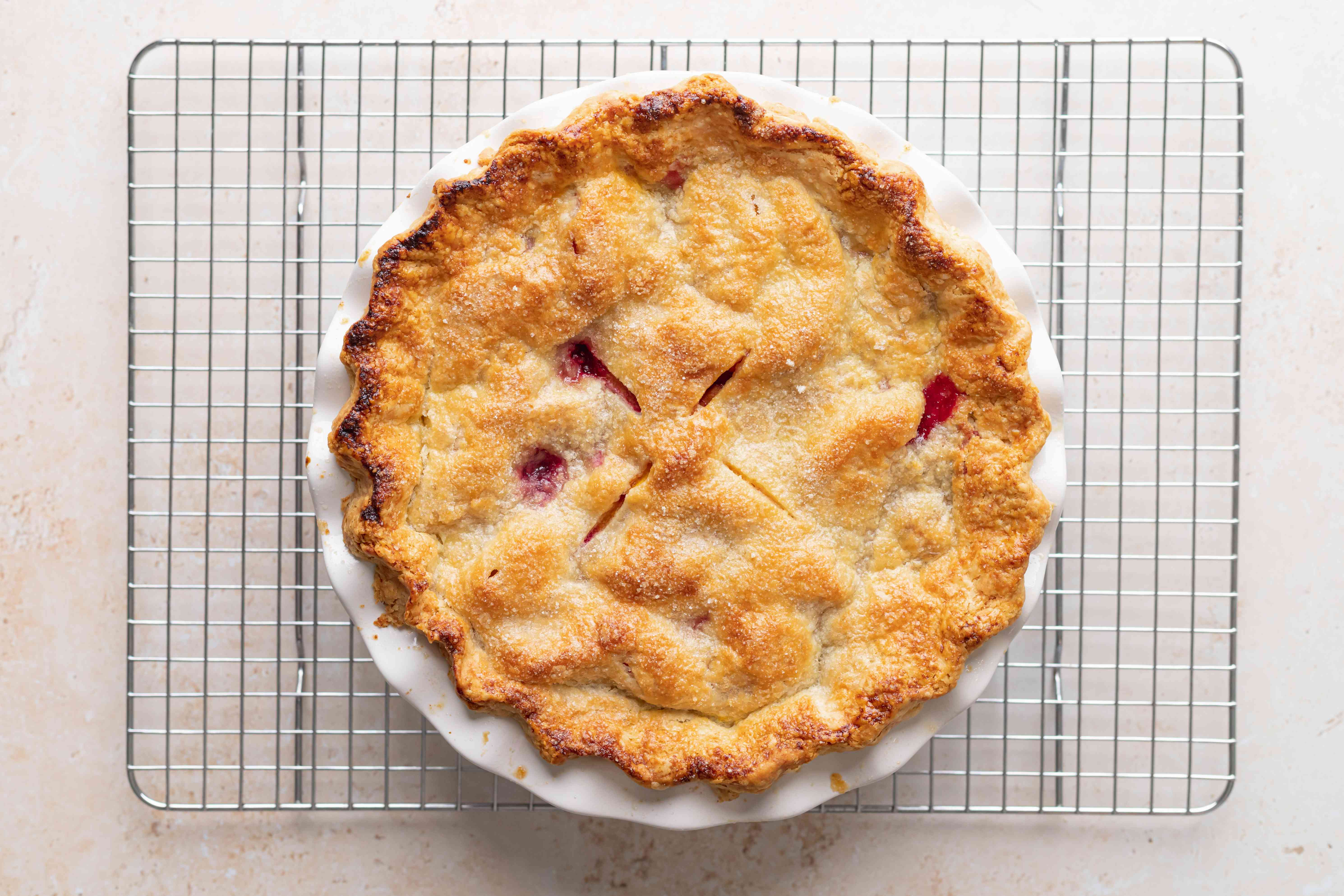 A stone fruit and berry pie cooling on a rack.