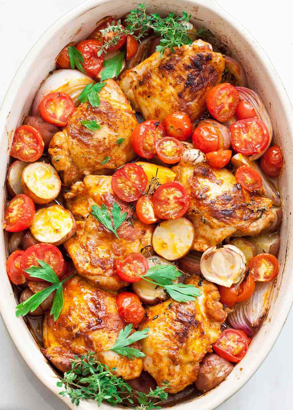 Paprika Chicken and Potatoes with Tomatoes in an oval baking dish