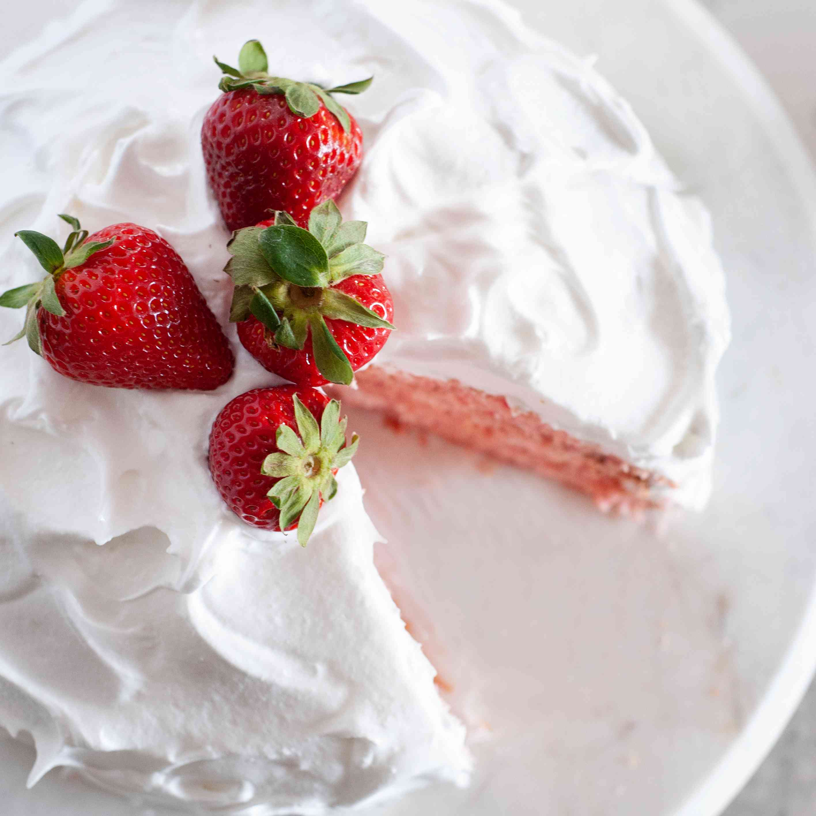 Strawberry Layer Cake Made with Fresh Strawberries set on a cake stand with a slice removed.