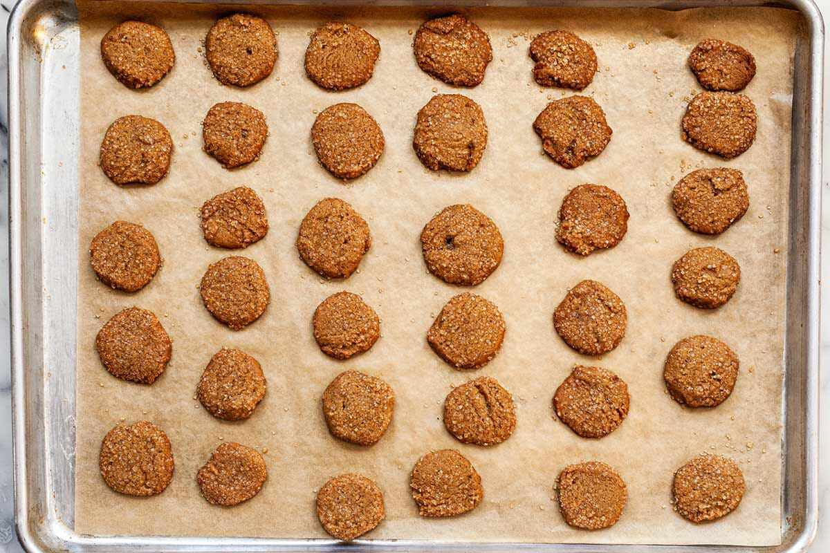 Slice and Bake Ginger Cookies cooling on a baking sheet covered with parchment.