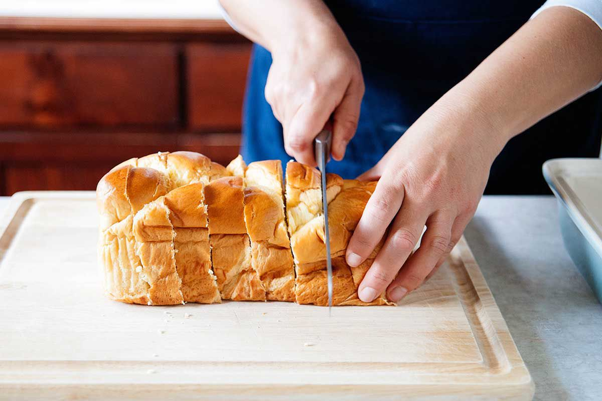 French Toast Bake Recipe - person slicing bread