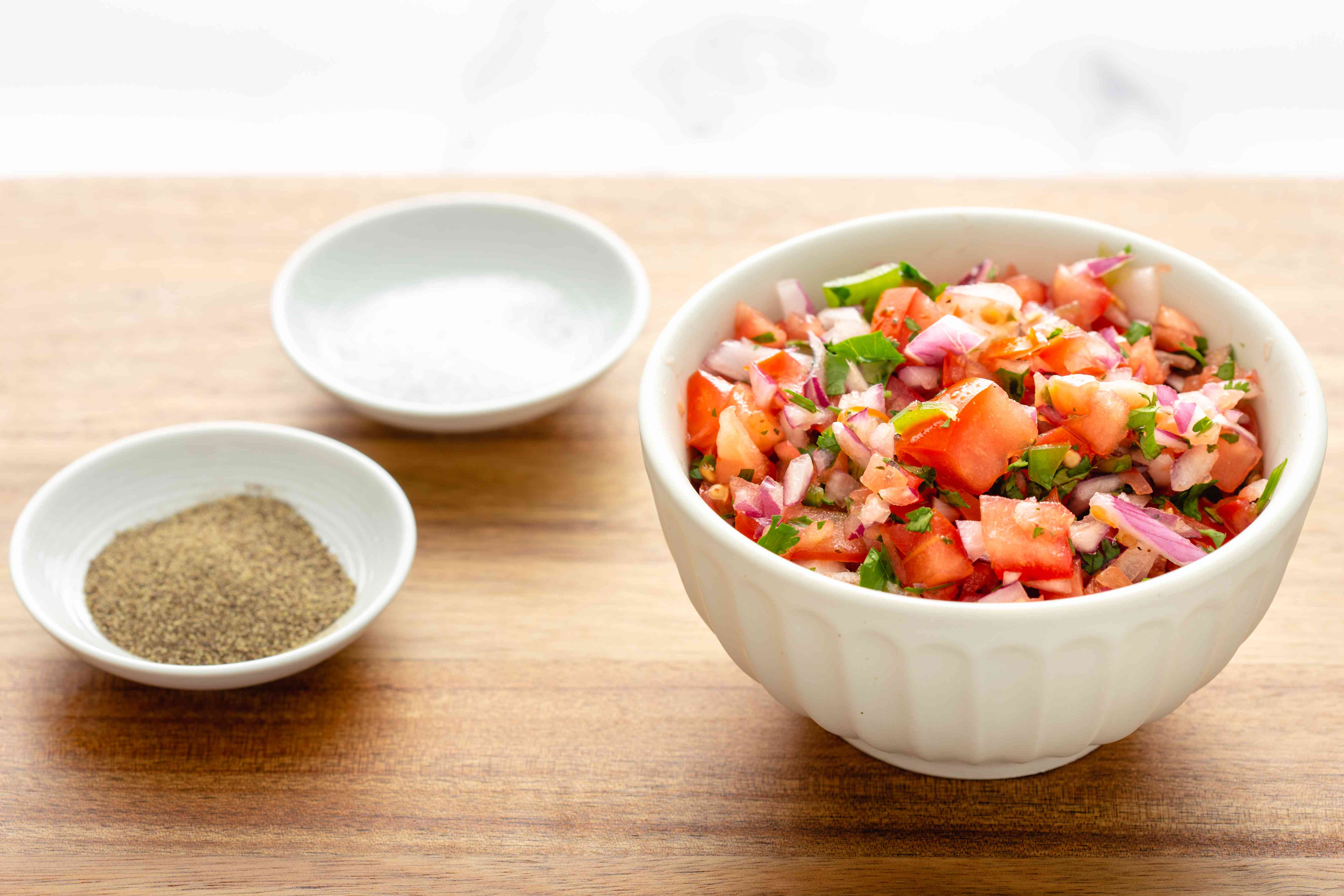 A bowl with salsa in a white bowl with salt and pepper next to it.