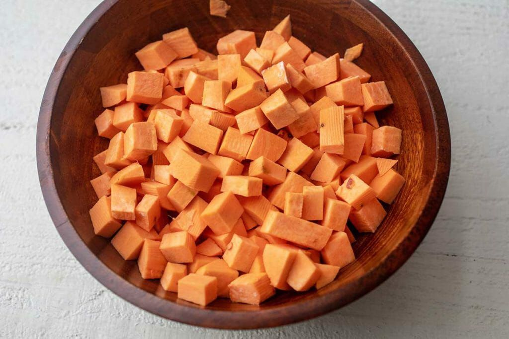 Chopped sweet potatoes in wooden bowl for cider-braised chicken thighs