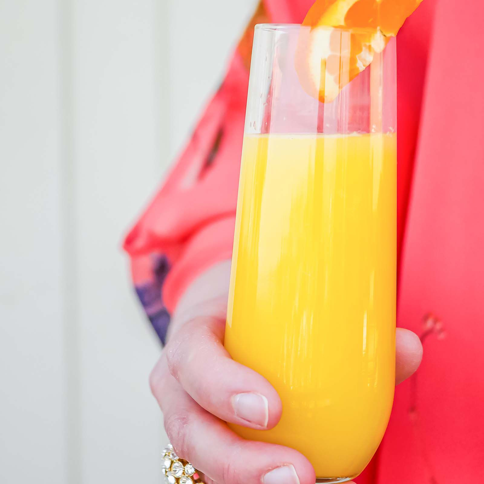 A person holding a mimosa for a DIY Mimosa Bar.