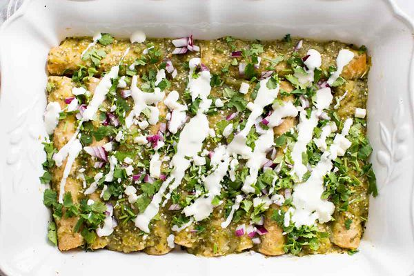 Finished Enchiladas Verdes Recipe Garnished with cheese, red onion, and fresh cilantro