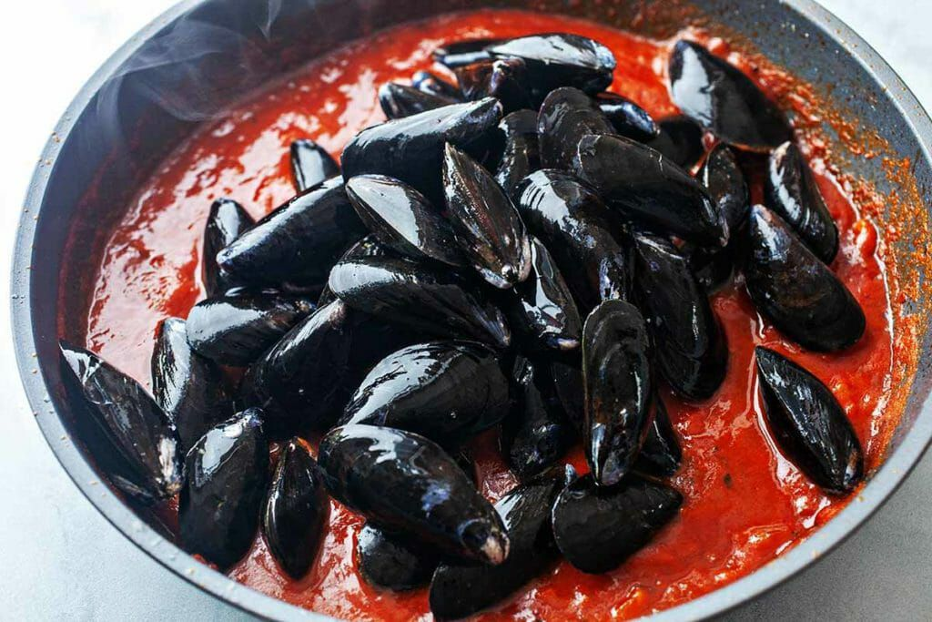 Spaghetti with mussels - mussels in pan of tomato sauce