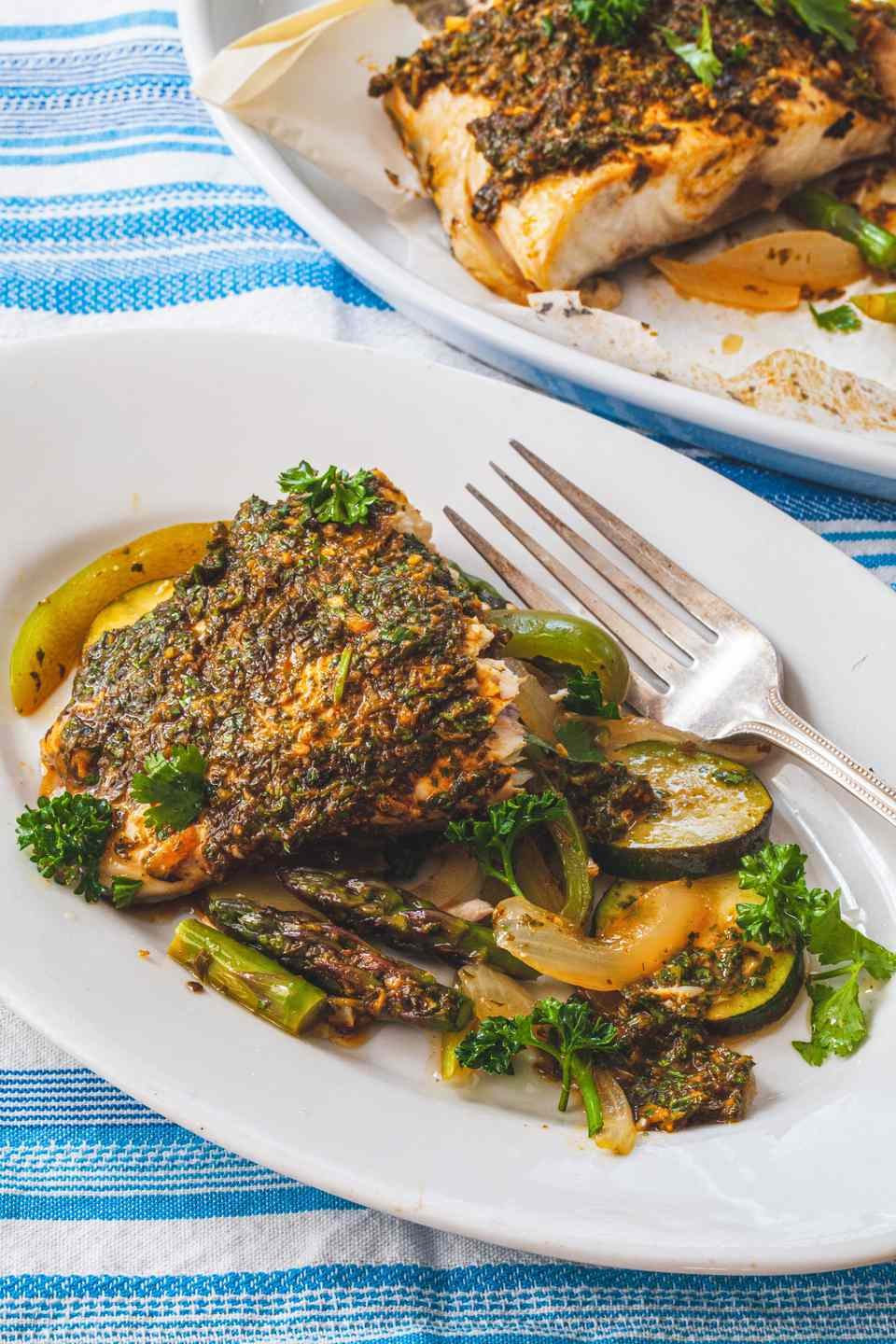 Parchment Baked Fish with North African Chermoula on a plate with a blue and white striped linen underneath.