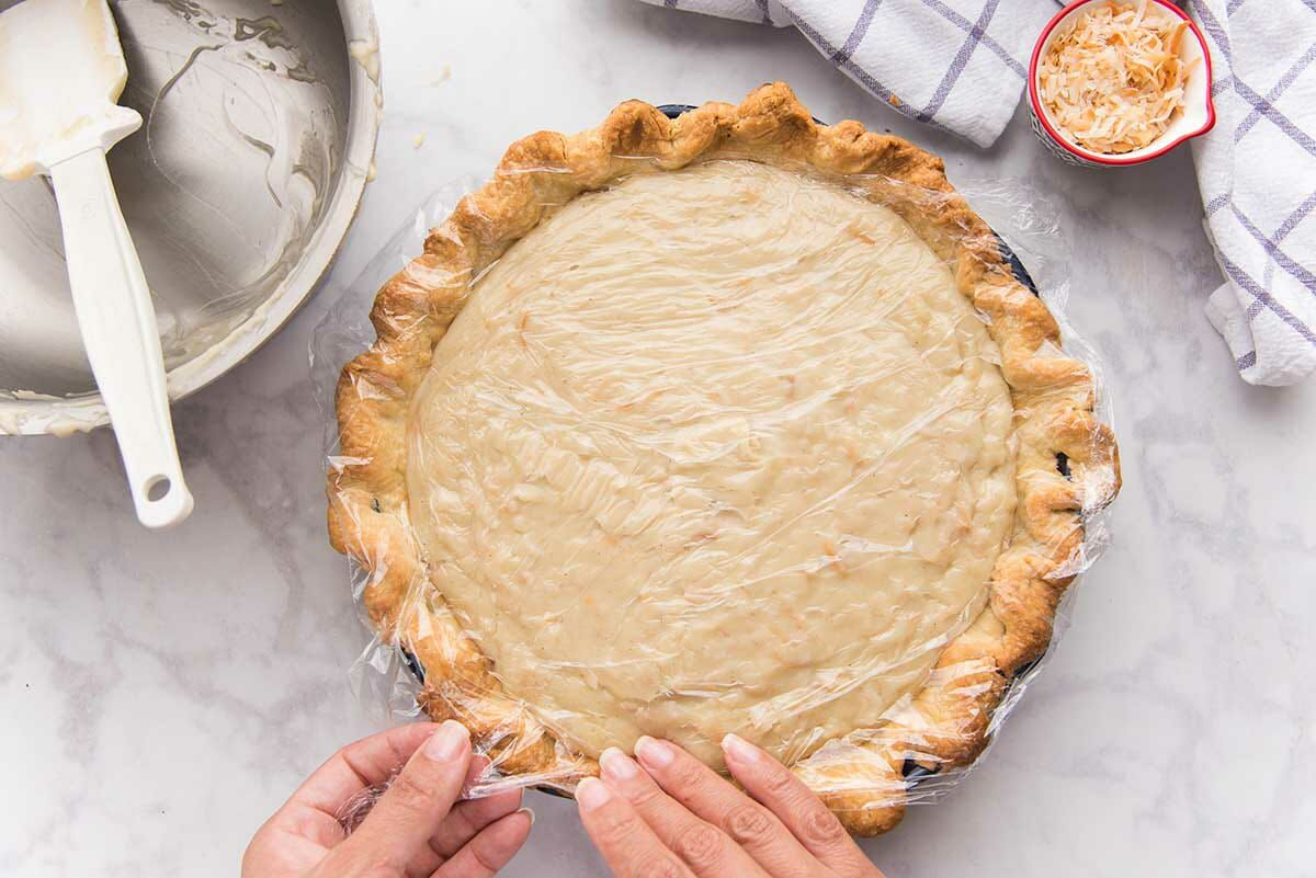 Saran wrap is placed on the top of the pie and filling for an easy coconut cream pie.