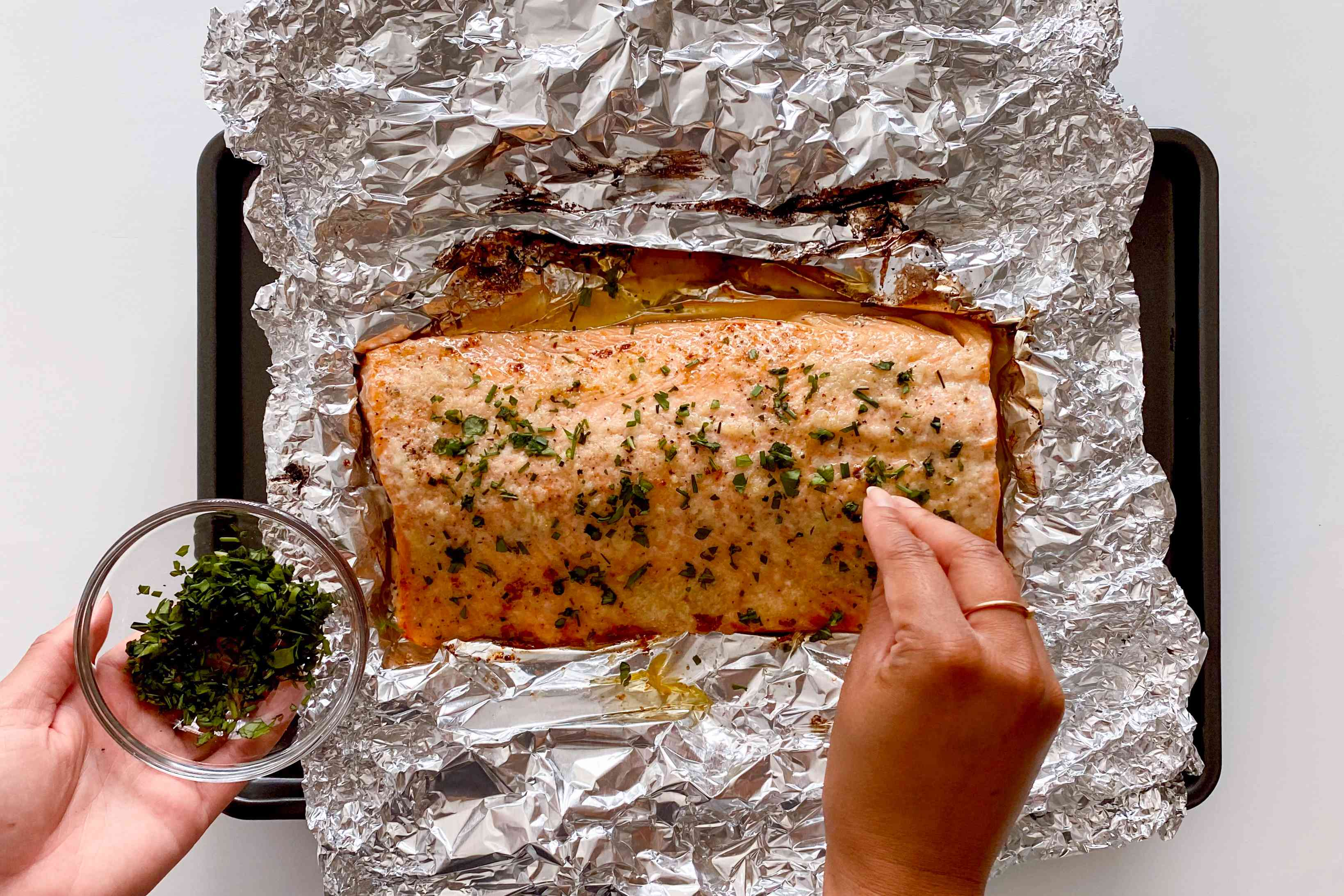 Sprinkling herbs on Honey Garlic Butter Roasted Salmon.
