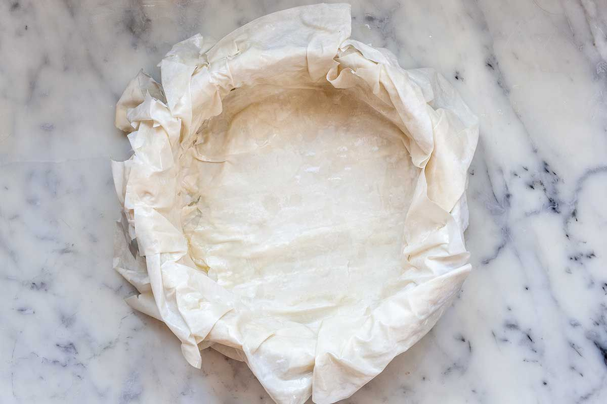 A cake pan is on a marble countertop. The phyllo is draped over the sides of the pan and covering the bottom..