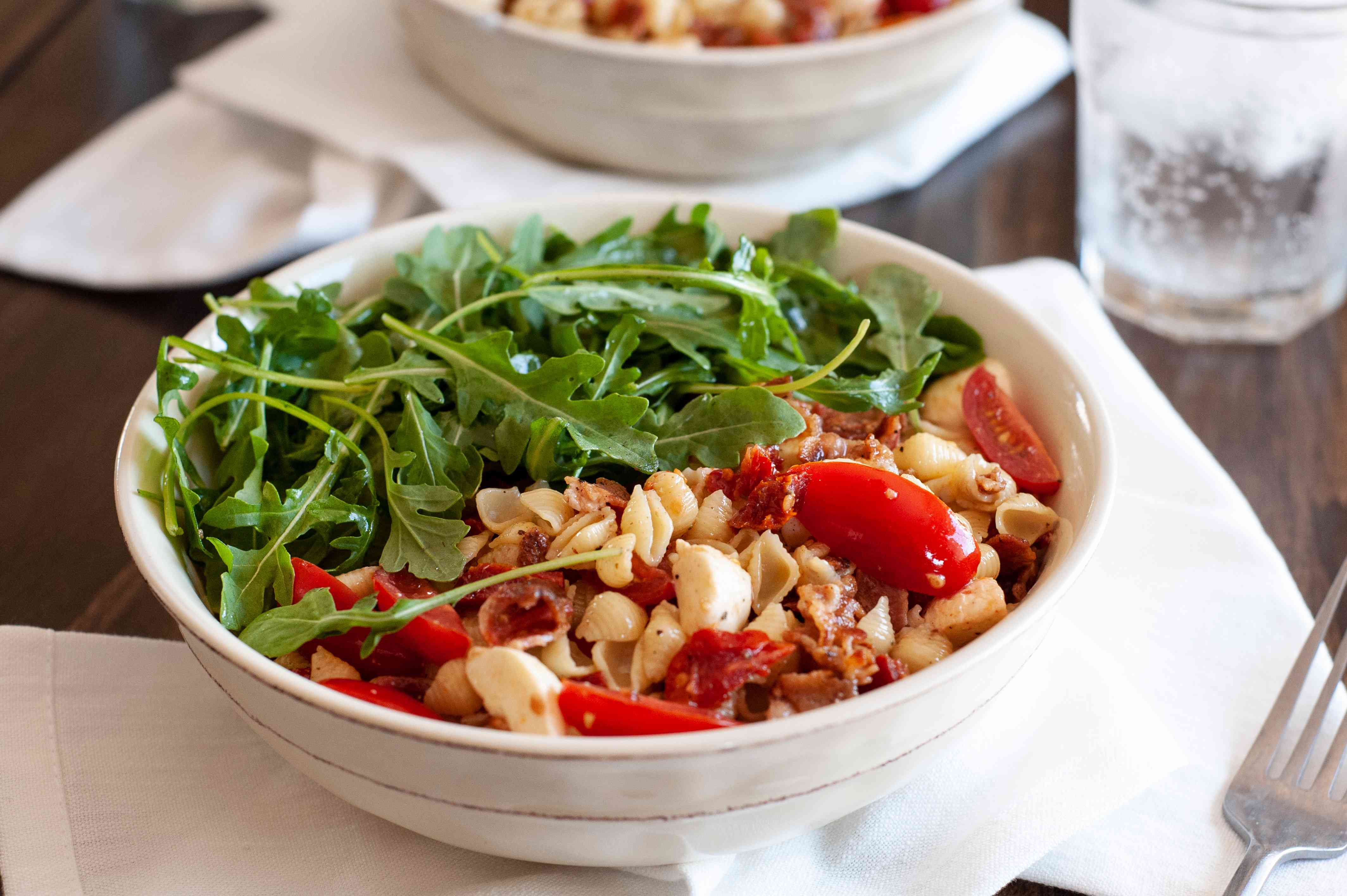 Summery blt pasta on a table with white linens, utensils and ice water.