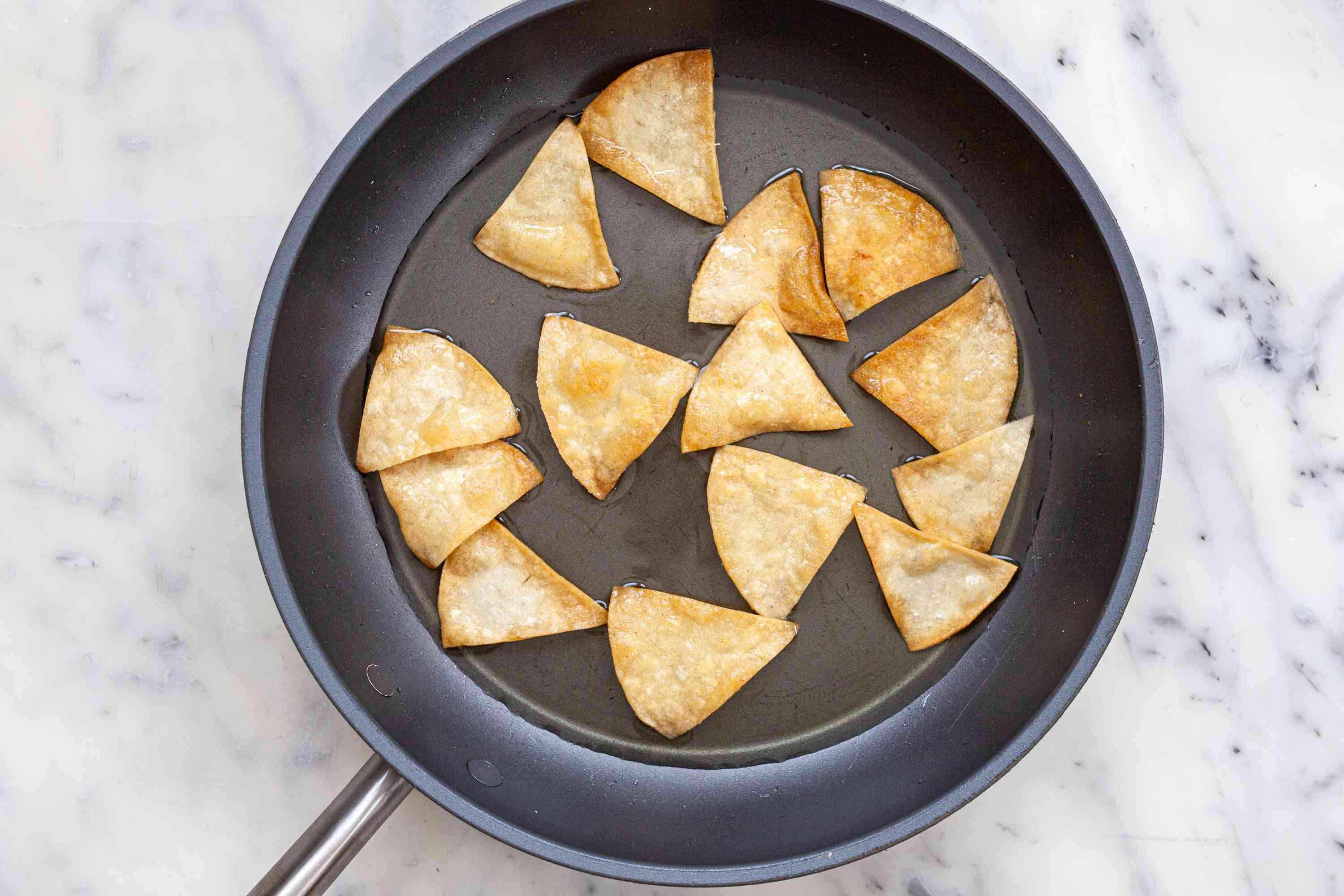 Tortilla chips frying in a skillet to make Chilaquiles.