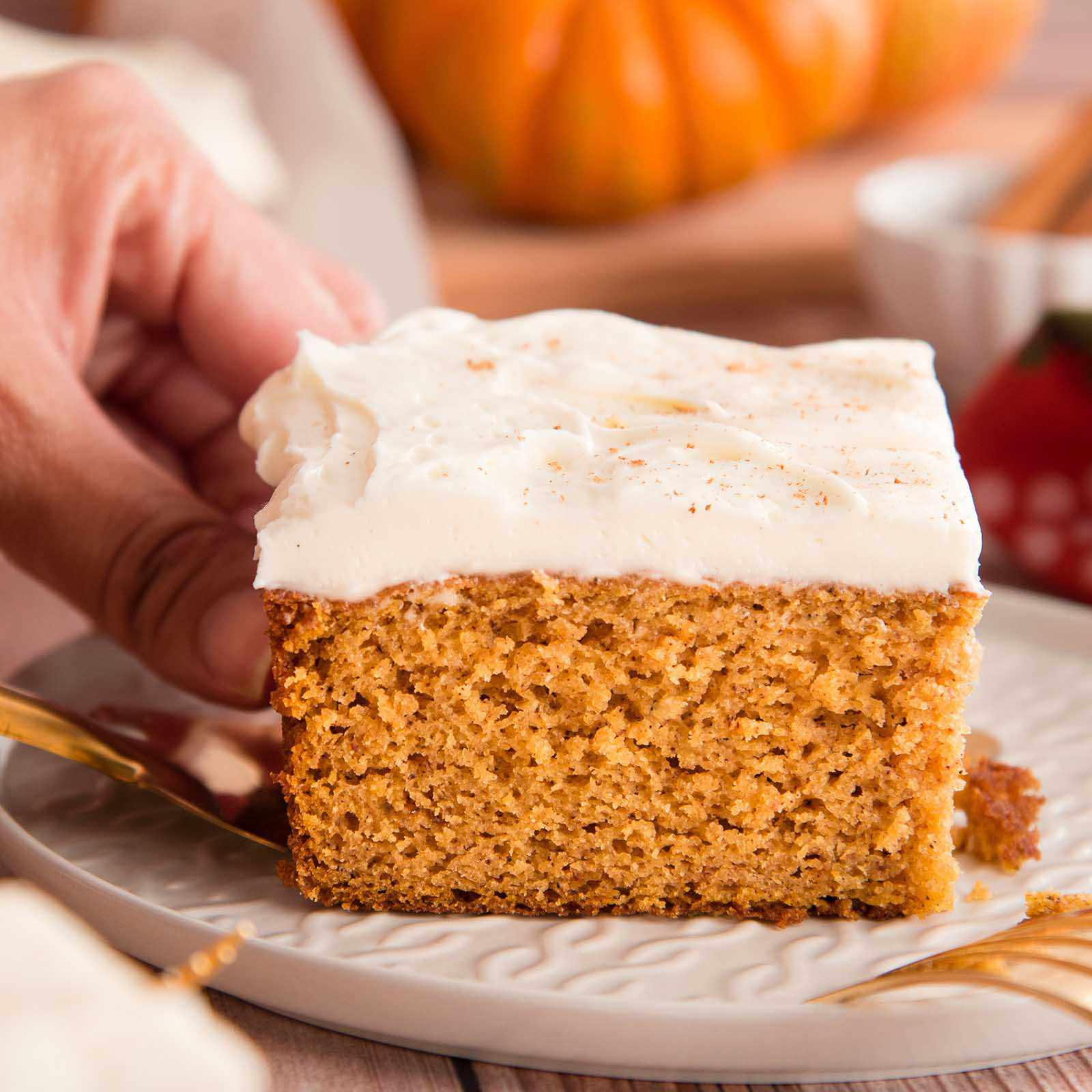 Side view of The Best Pumpkin Cake with Cream Cheese Frosting being placed on a plate.