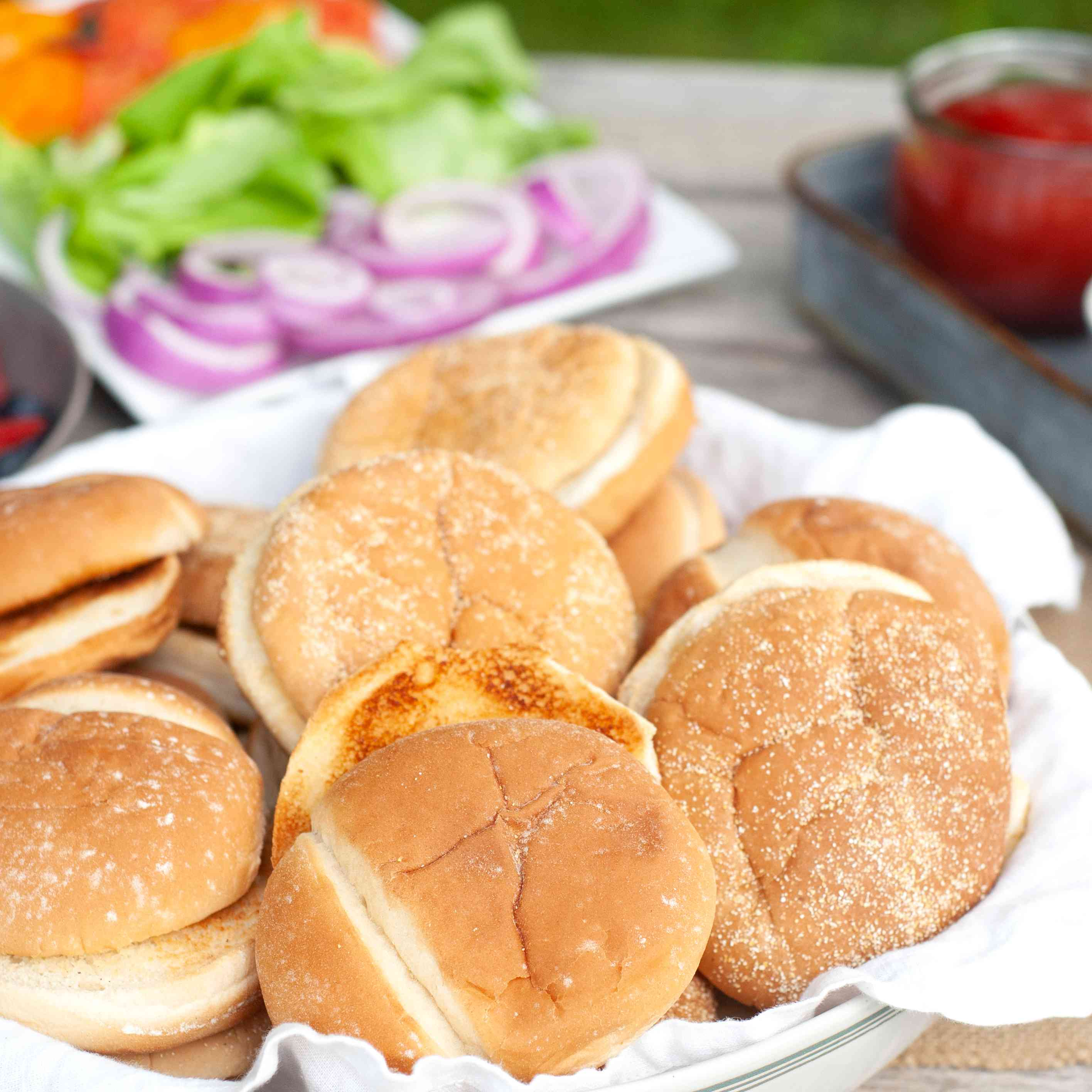 A tray full of homemade hamburger buns with sliced tomato, onion, and lettuce in the backgroun.