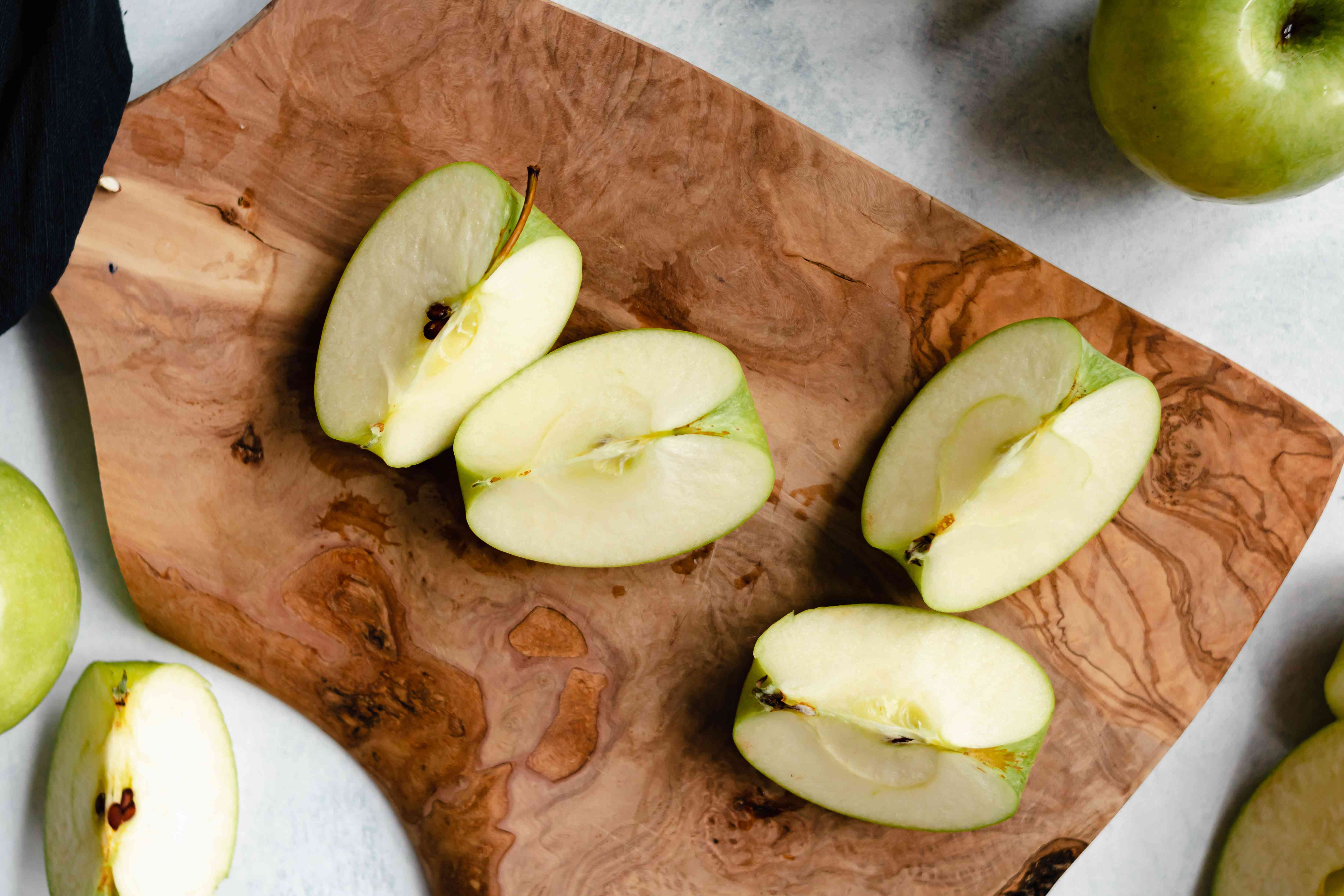 Chopped apples on a wooden cutting board to make an apple butter recipe.