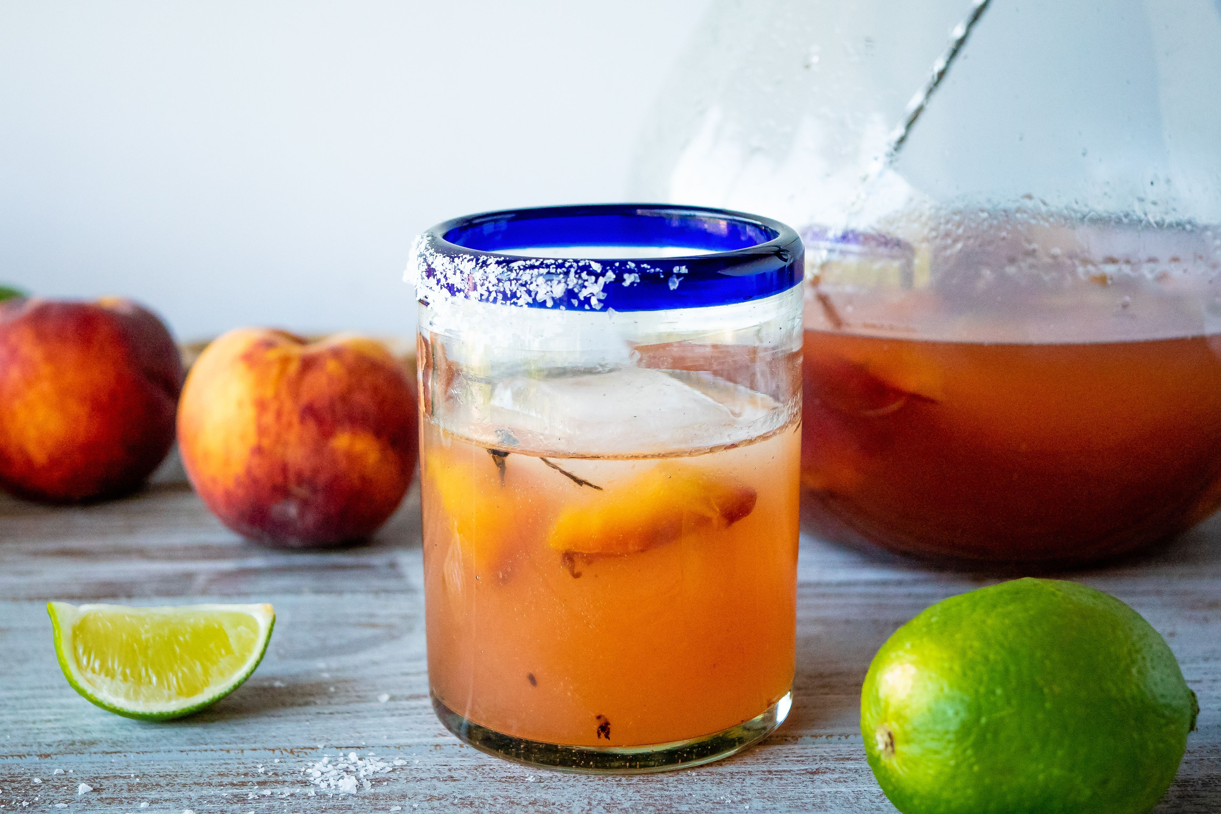 Grilled peach margarita on a table with limes and peaches.