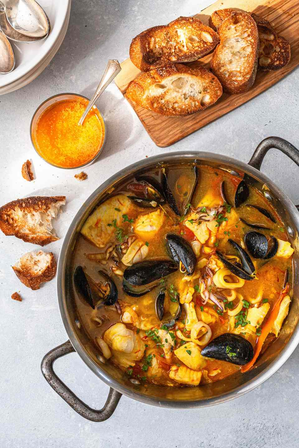 Overhead view of a pot of bouillabaisse and bread.