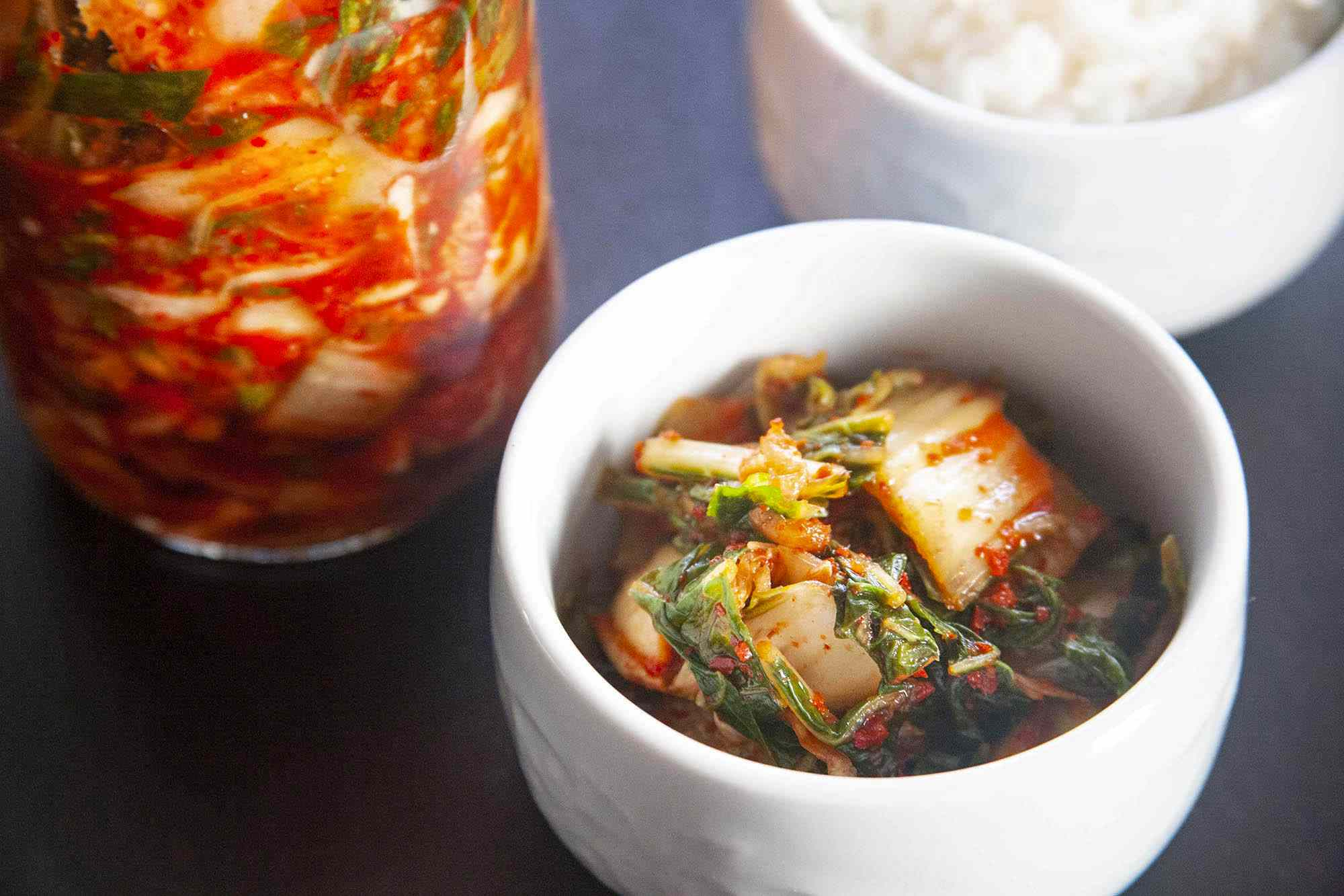 A bowl with easy homemade kimchi is in front of the jar of it and white rice is behind it.