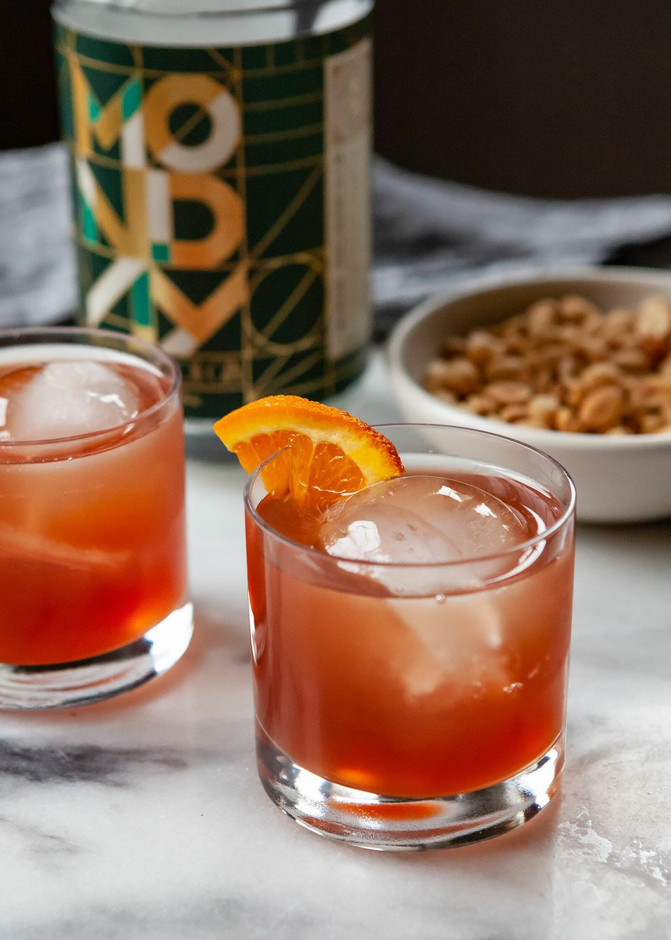 Non alcoholic negroni in a rocks glass with ice and an orange wedge. Bar nuts, and the non alcoholic gin are pictured behind the glass.