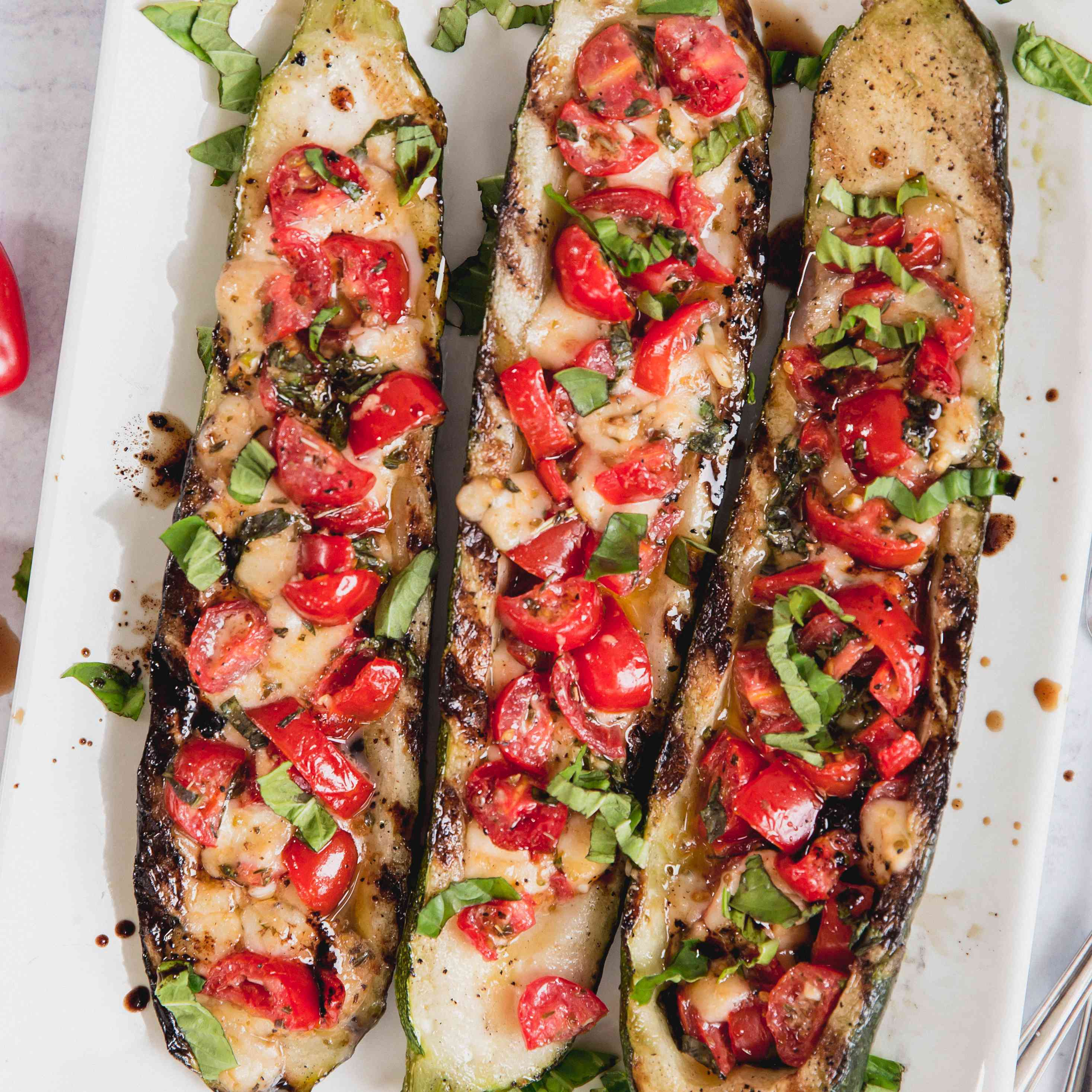 Overhead view of grilled zucchini with tomatoes, mozzarella, and basil served on a white platter.