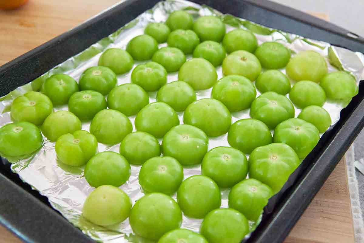 halved tomatillos cut side down on roasting tray