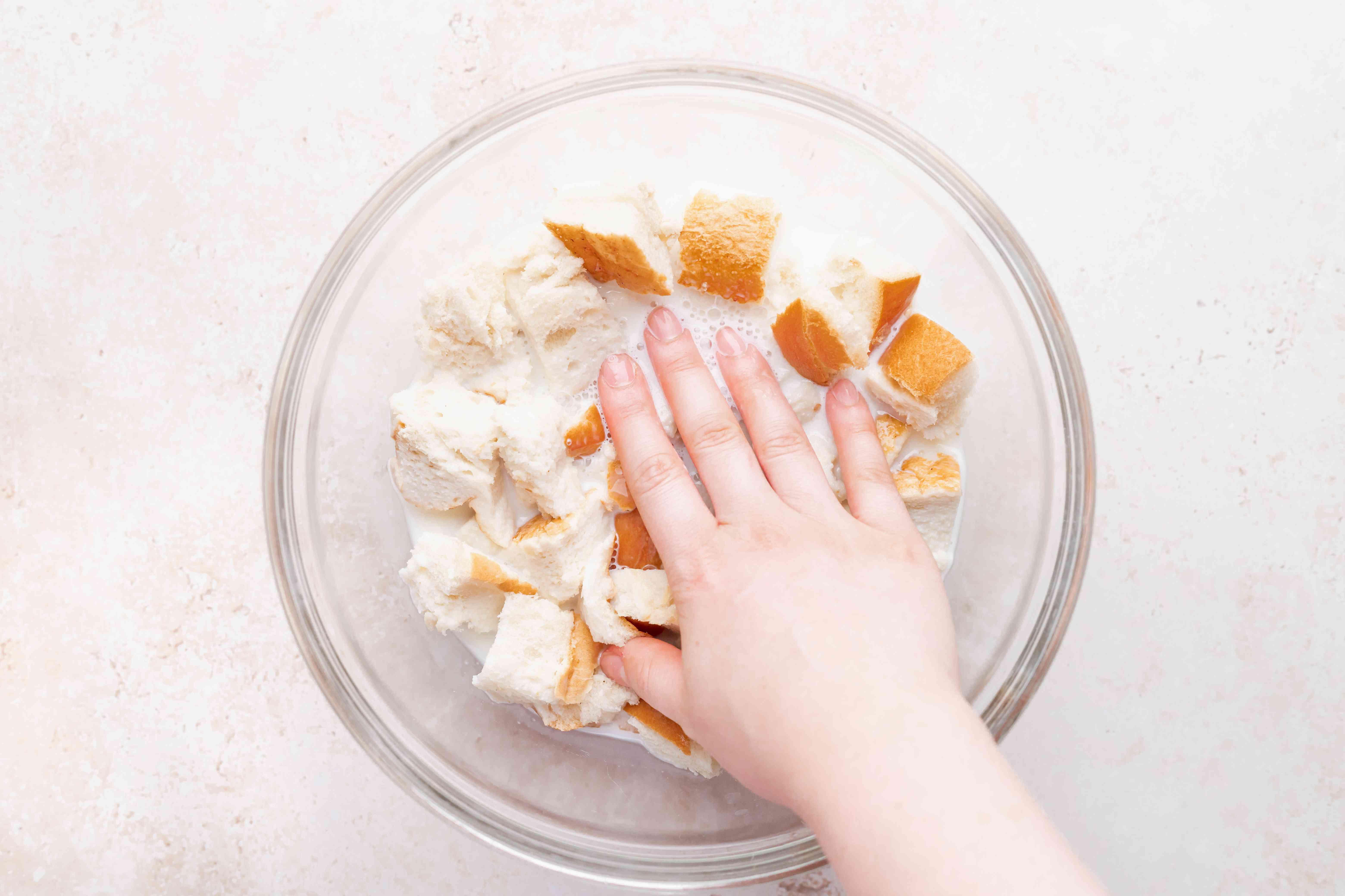 Soaking bread in a milk mixture to make a bread pudding recipe.