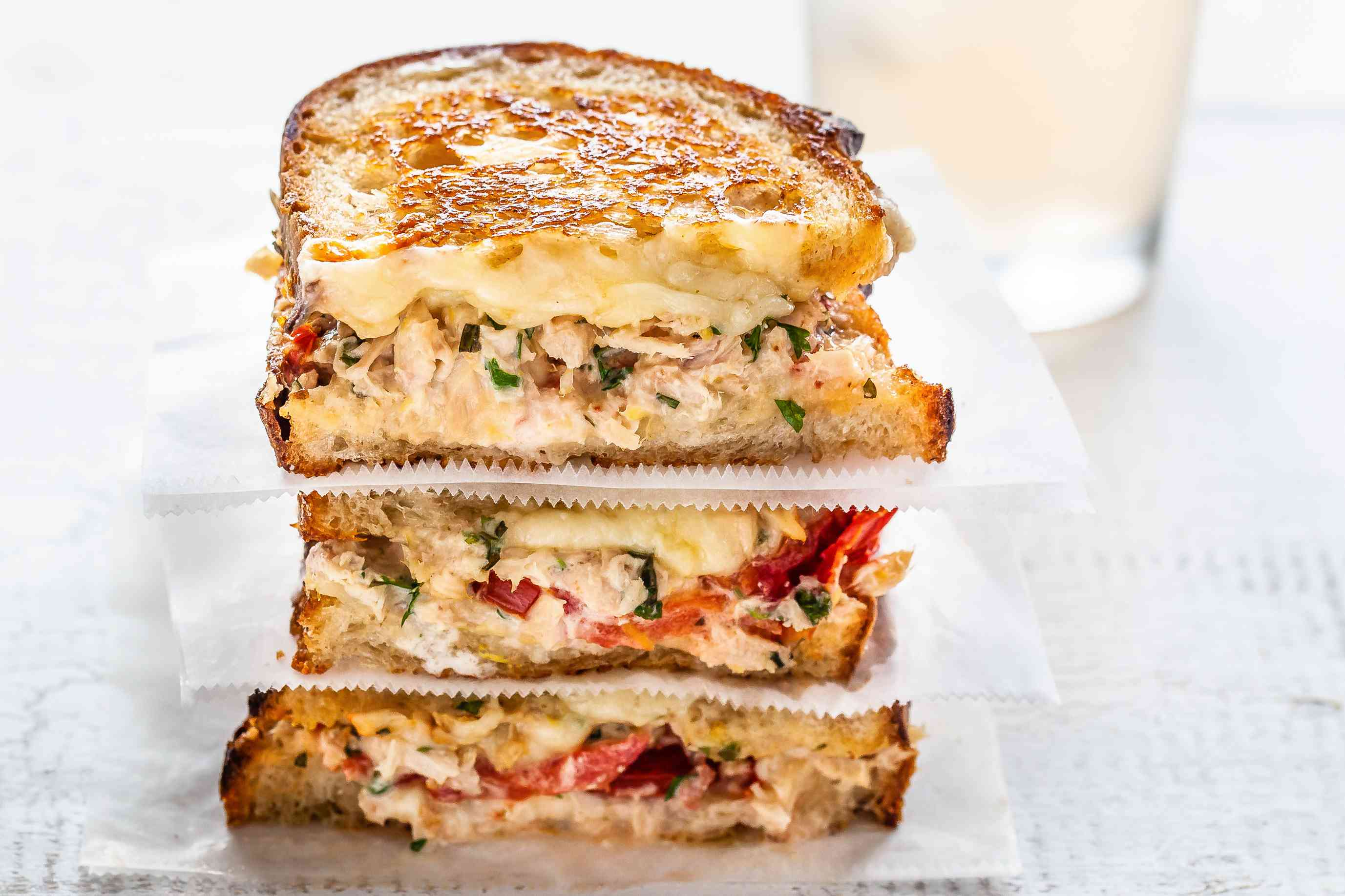 Stack of cheesy tuna melts separated with parchment paper on a table