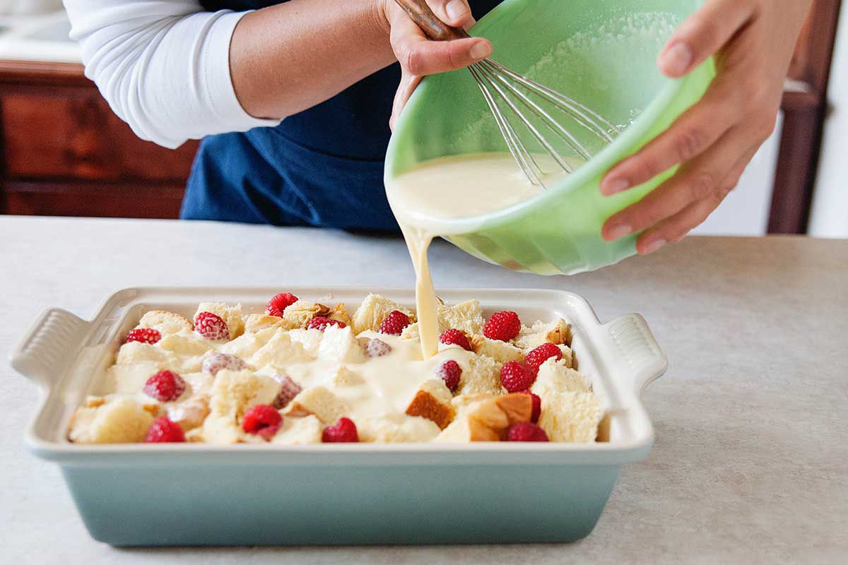 Overnight French Toast Casserole - custard being poured into casserole dish filled with bread