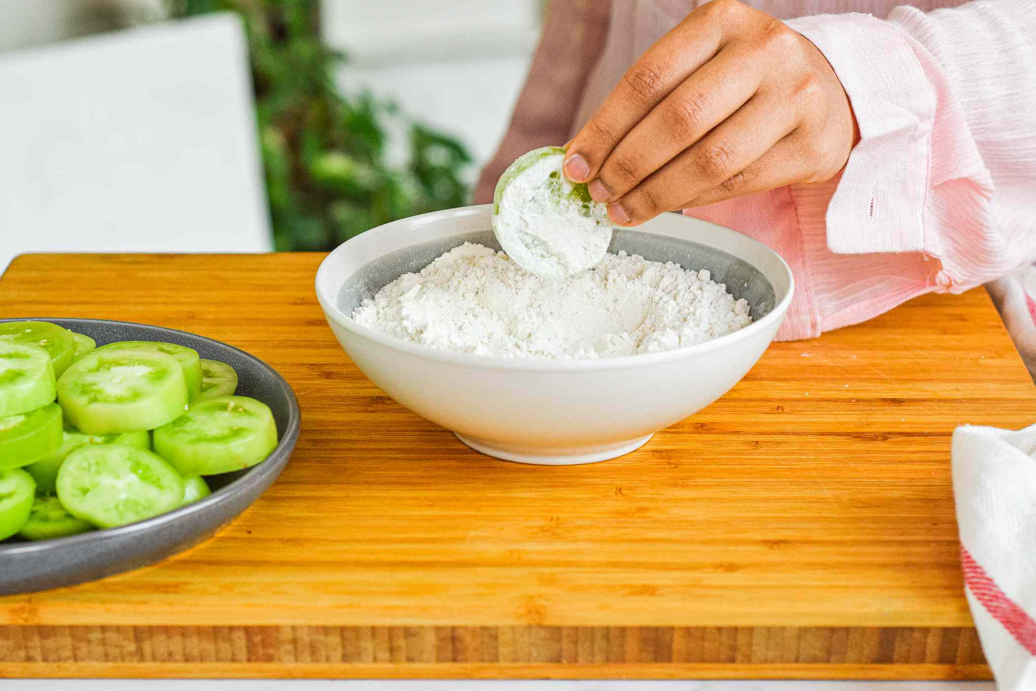 Dipping green tomatoes in flour mixture.