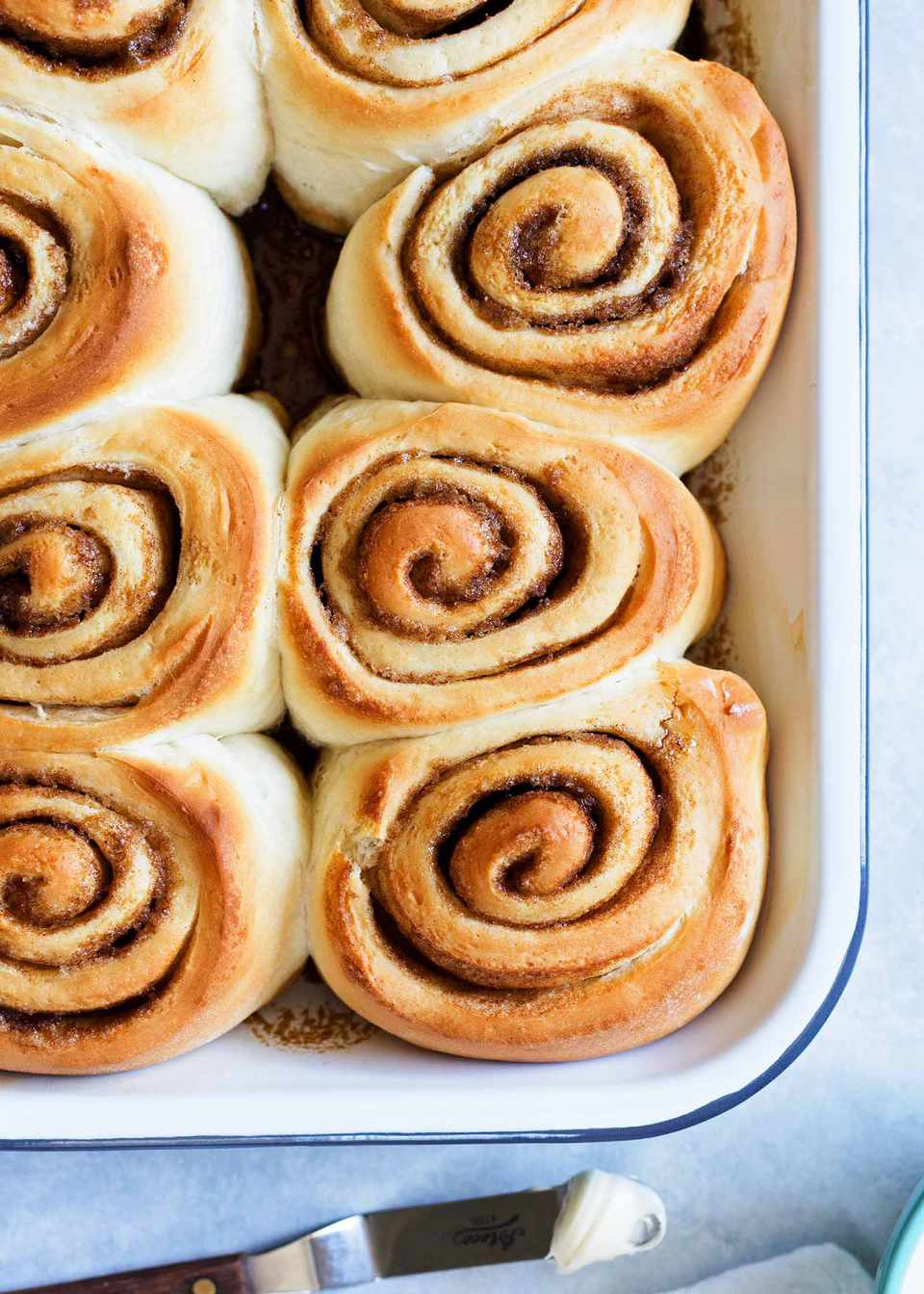The best cinnamon rolls baked and golden brown in a pan.