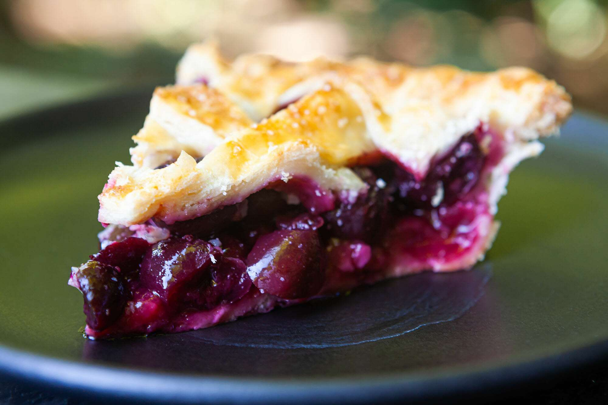 A slice of a cherry pie with a fresh cherry filling visible on the plate.