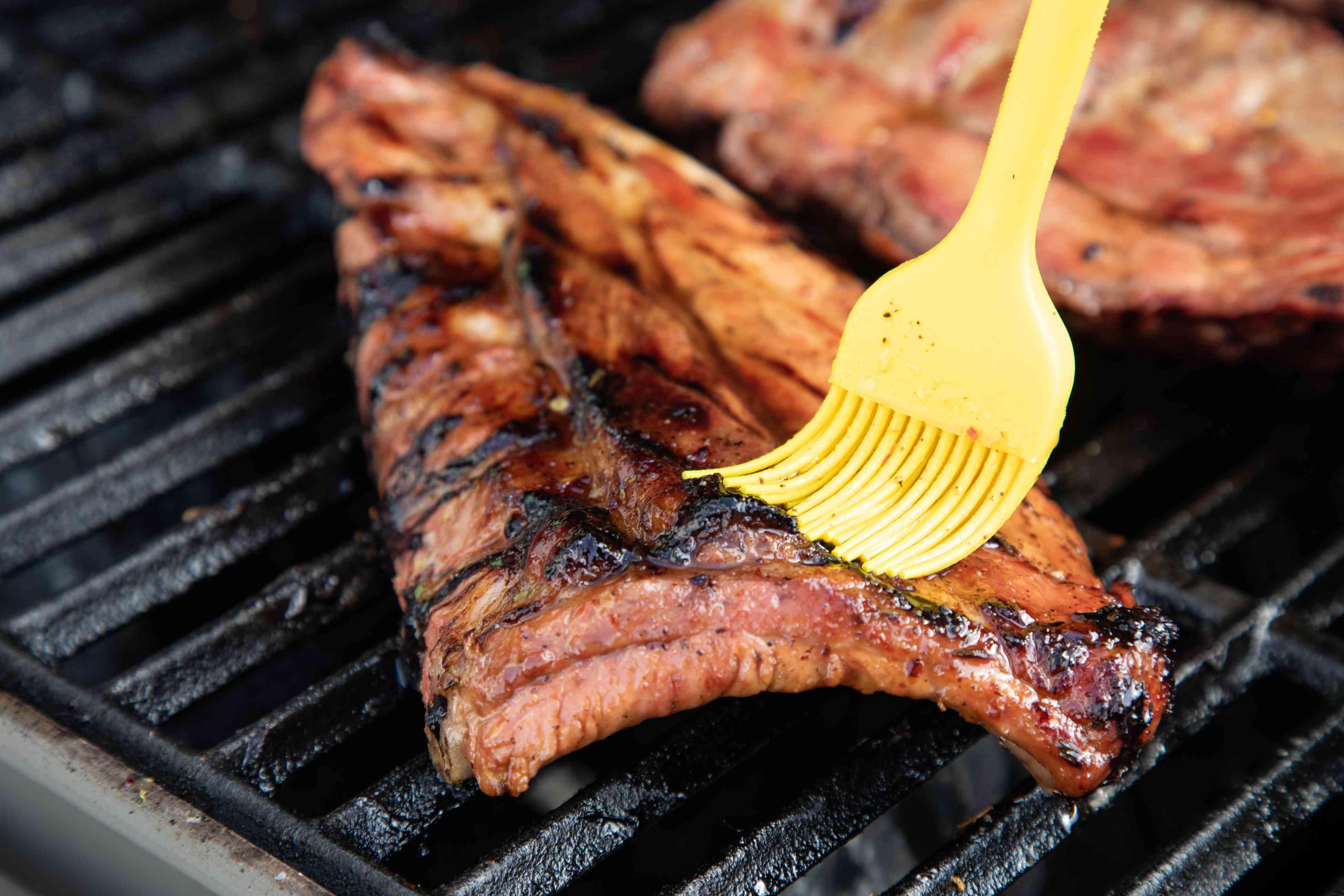 Basting grilled bbq ribs.