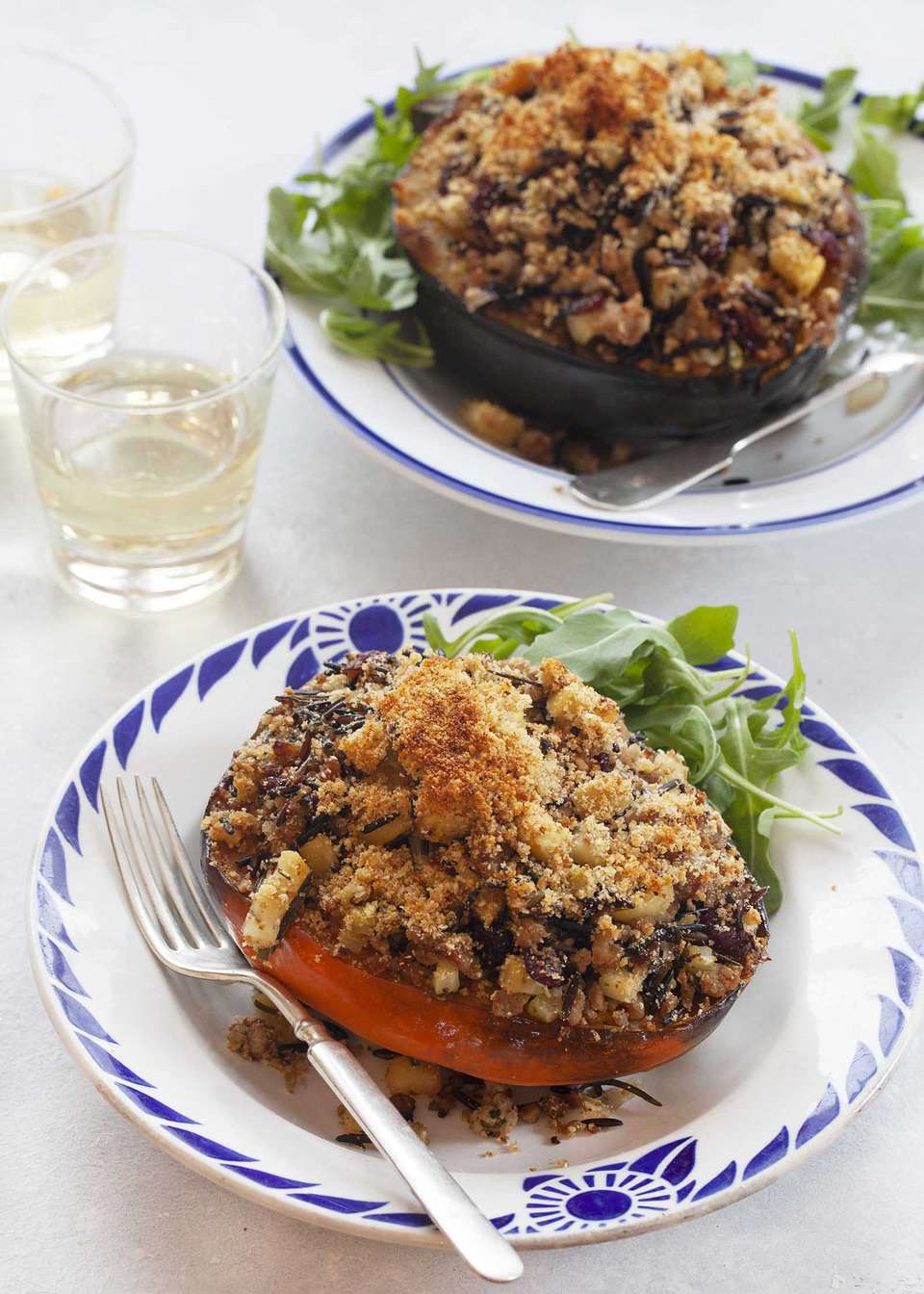 Easy Stuffed Squash: Acorn Squash on a plate stuffed with turkey sausage and rice. A glass is nearby filled with white wine.