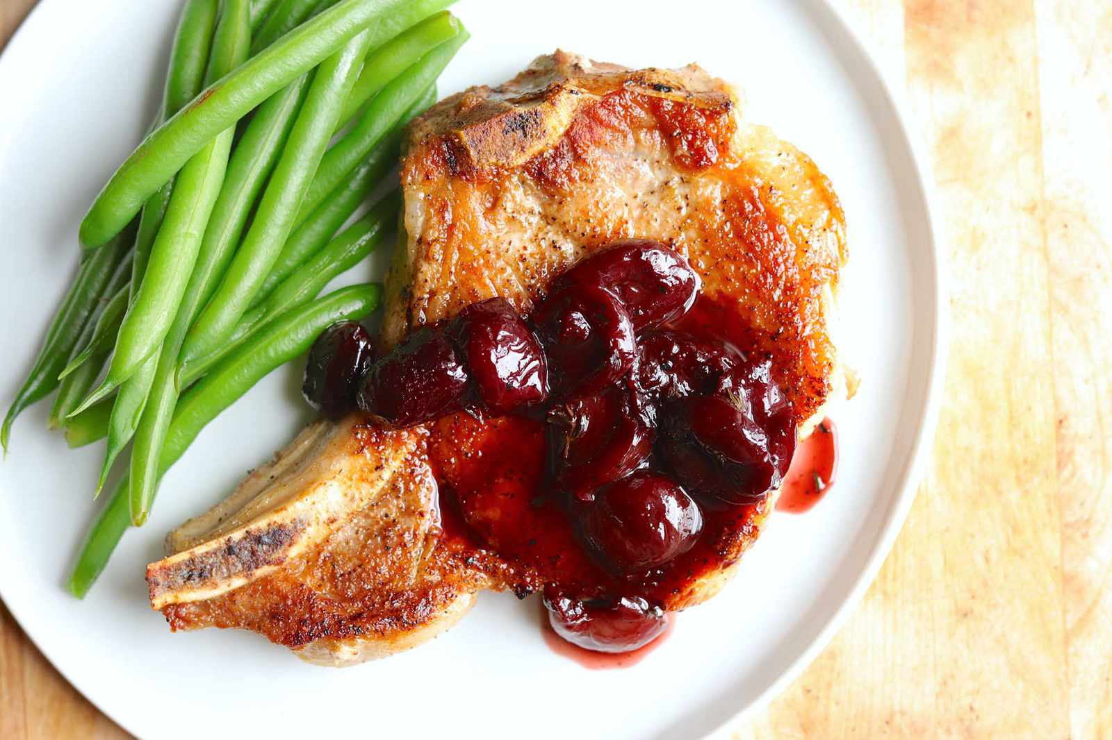 Overhead view of a a stove top pork chop topped with cherry sauce with a side of green beans.