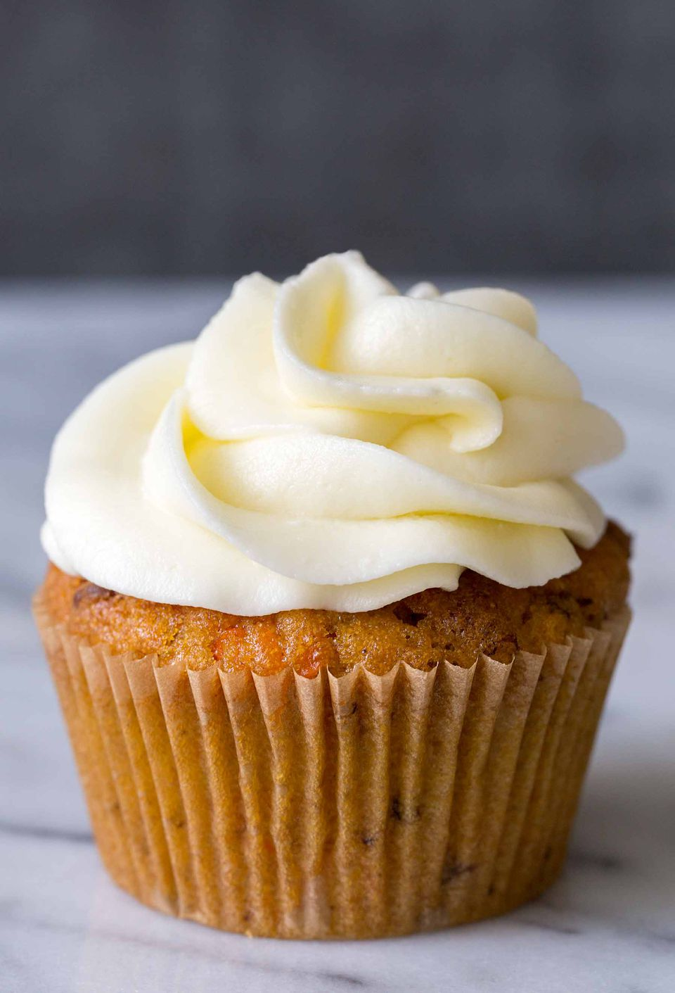 One single carrot cake cupcake topped with cream cheese frosting