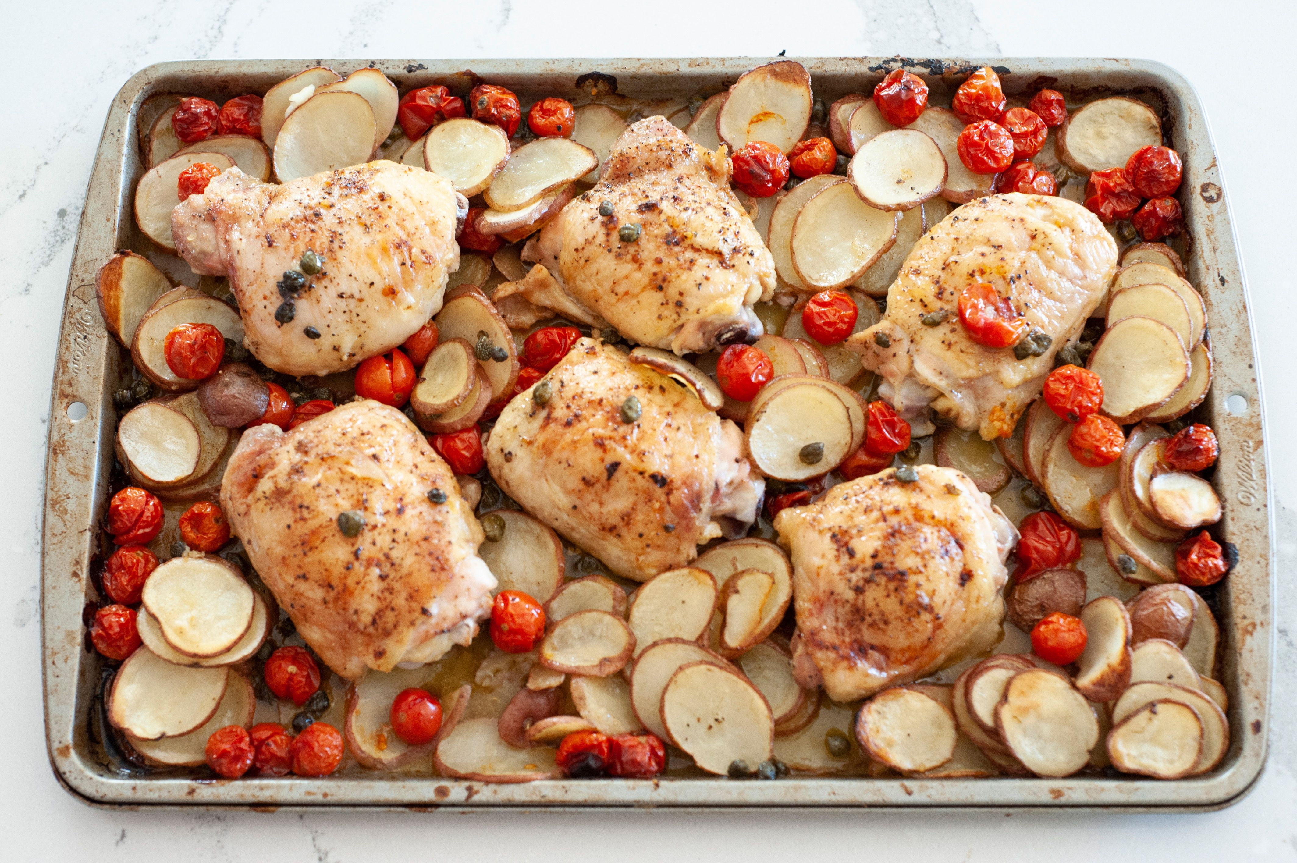 Sheet pan chicken thighs with tomatoes, potatoes, capers, and basil on a pan.