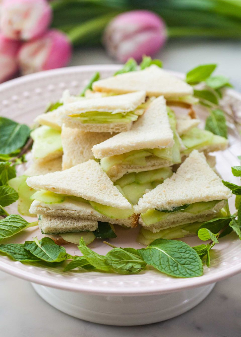 Side view of cucumber finger sandwiches stacked on a cake plate. The sandwiches are cut into triangles and slices of cucumber are visible layered inside each one.
