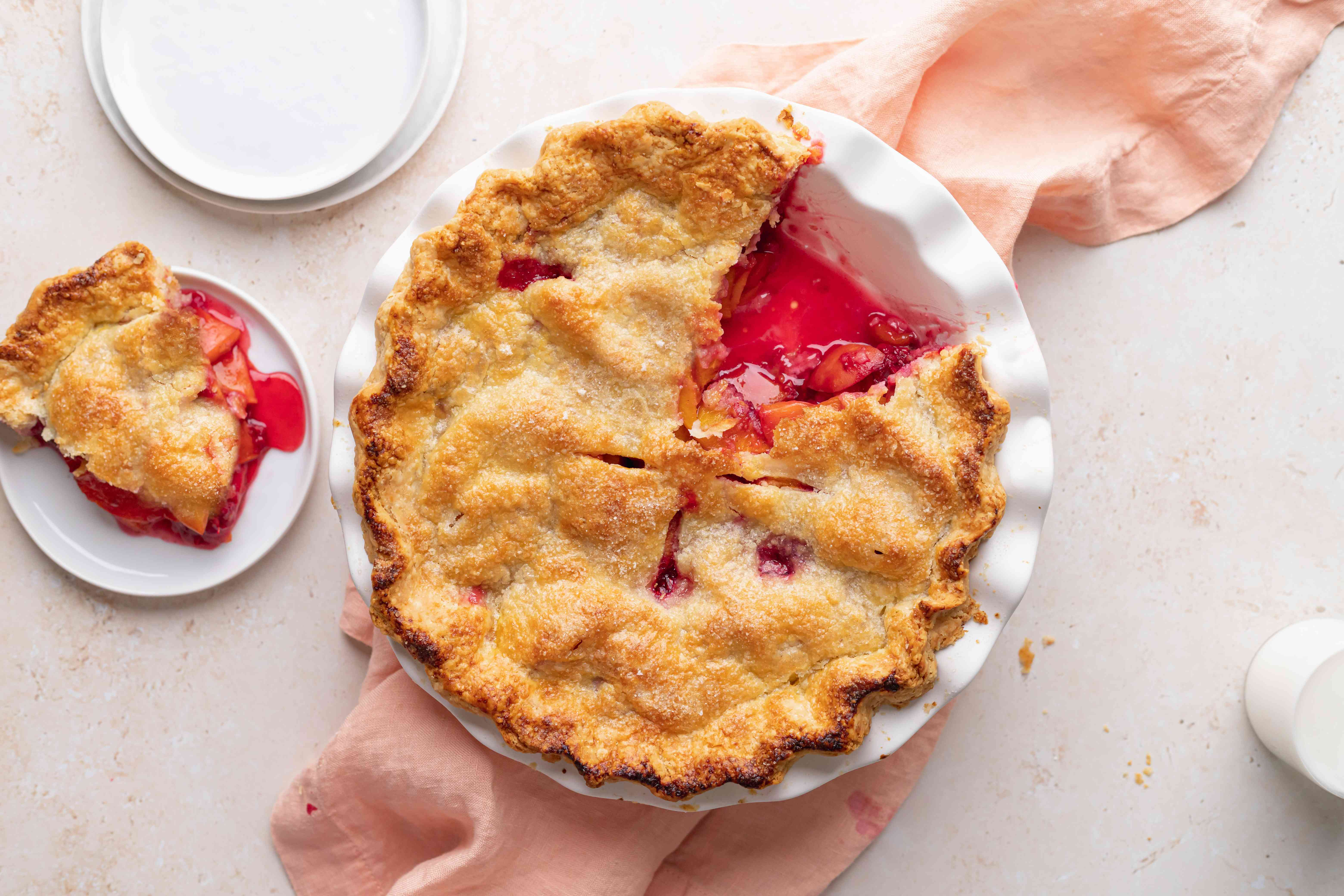 Overhead view of a summer peach and raspberry pie.