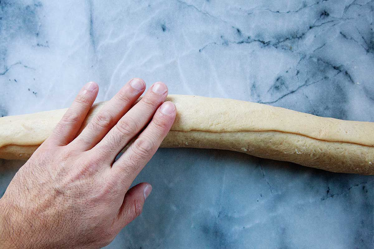 The best King Cake dough is rolled into a tube shape with a hand resting on top. The dough rests on a marble background.