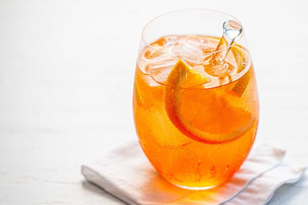 A wine glass with an Aperol spritz cocktail inside.