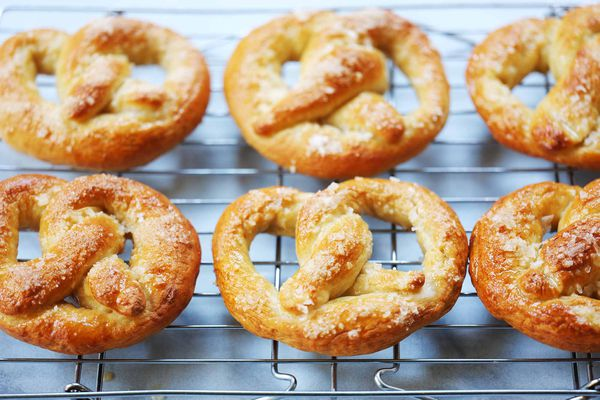 Six Philly soft pretzels cooling on a cooling rack