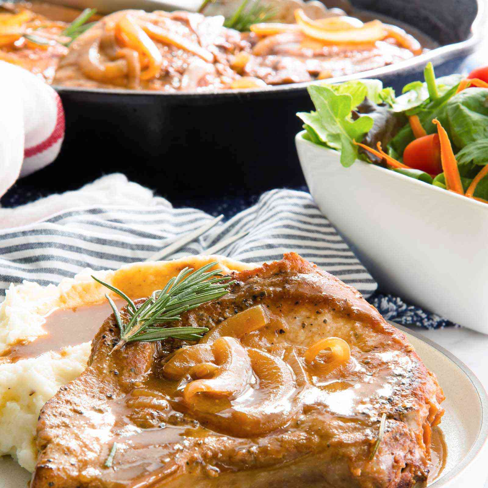 A gluten free smothered pork chop with a pile of mashed potatoes covered in gravy on an ivory plate with a striped linen nearyby and a side salad.